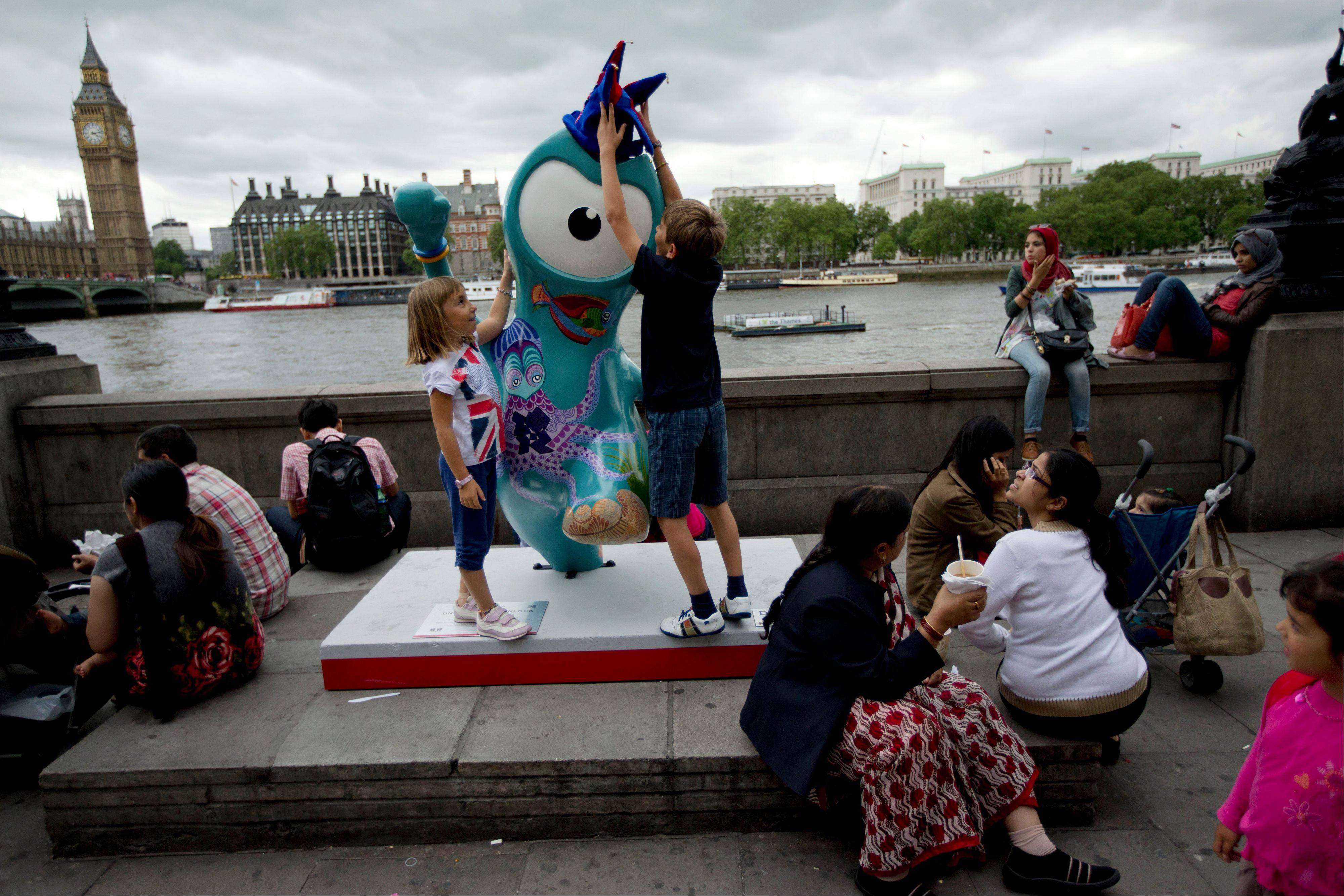 Children play with a statue of Wenlock, the Olympic mascot for the 2012 Olympics in London.