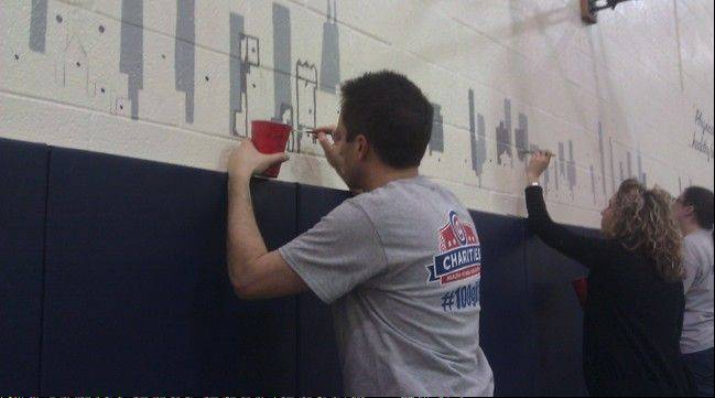 Cubs employees paint a mural at Casals School in Chicago during a Cubs Caravan stop on Thursday,