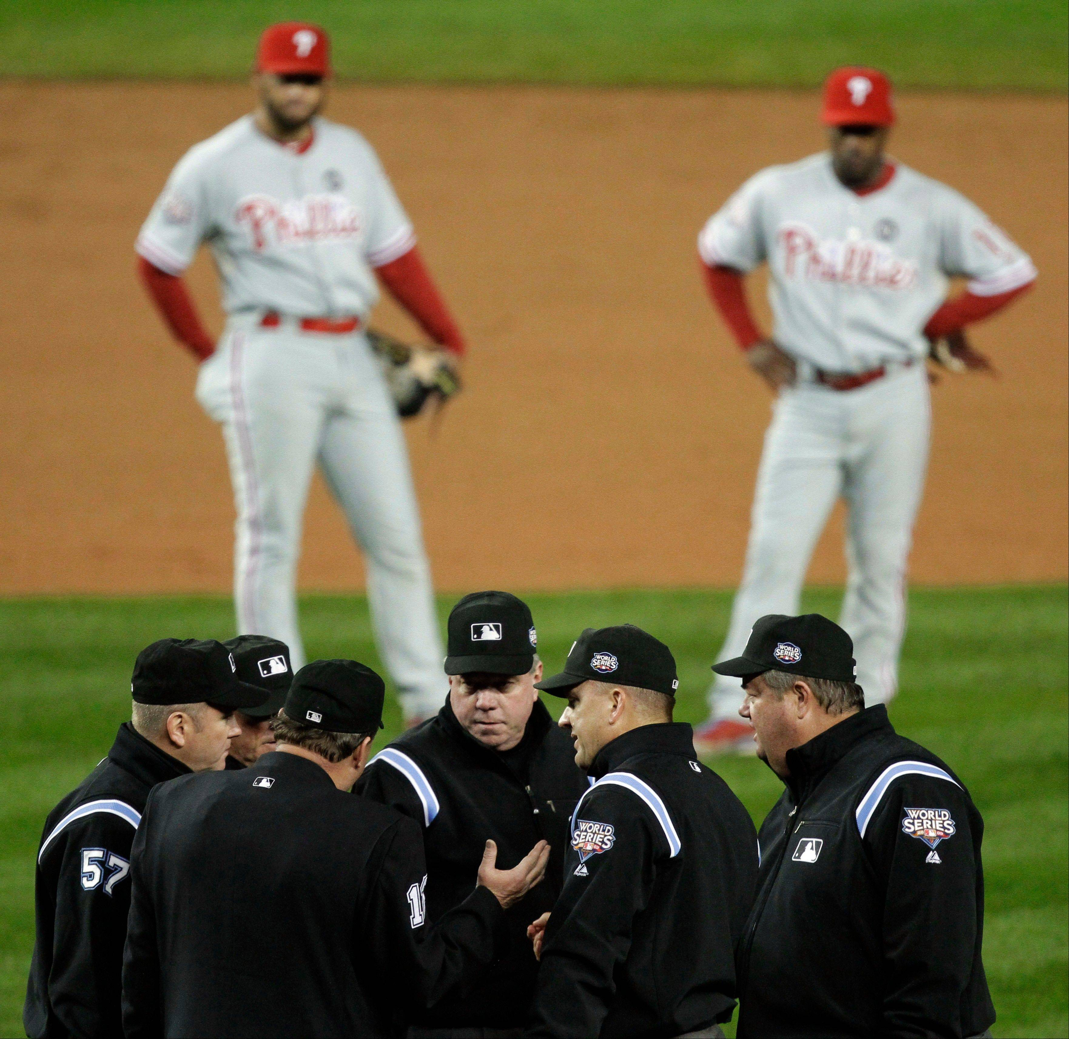 FILE - In this Oct. 28, 2009, file photo, Philadelphia Phillies' Pedro Feliz, left, and Jimmy Rollins watch in the background, as umpires discuss a call at first base during the fifth inning in Game 1 of the baseball's World Series against the New York Yankees in New York. Major League Baseball announced Thursday, Jan. 16, 2014, that it will greatly expand instant replay to review close calls starting this season. Each manager will be allowed to challenge at least one call per game. If he's right, he gets another challenge. After the seventh inning, a crew chief can request a review on his own.