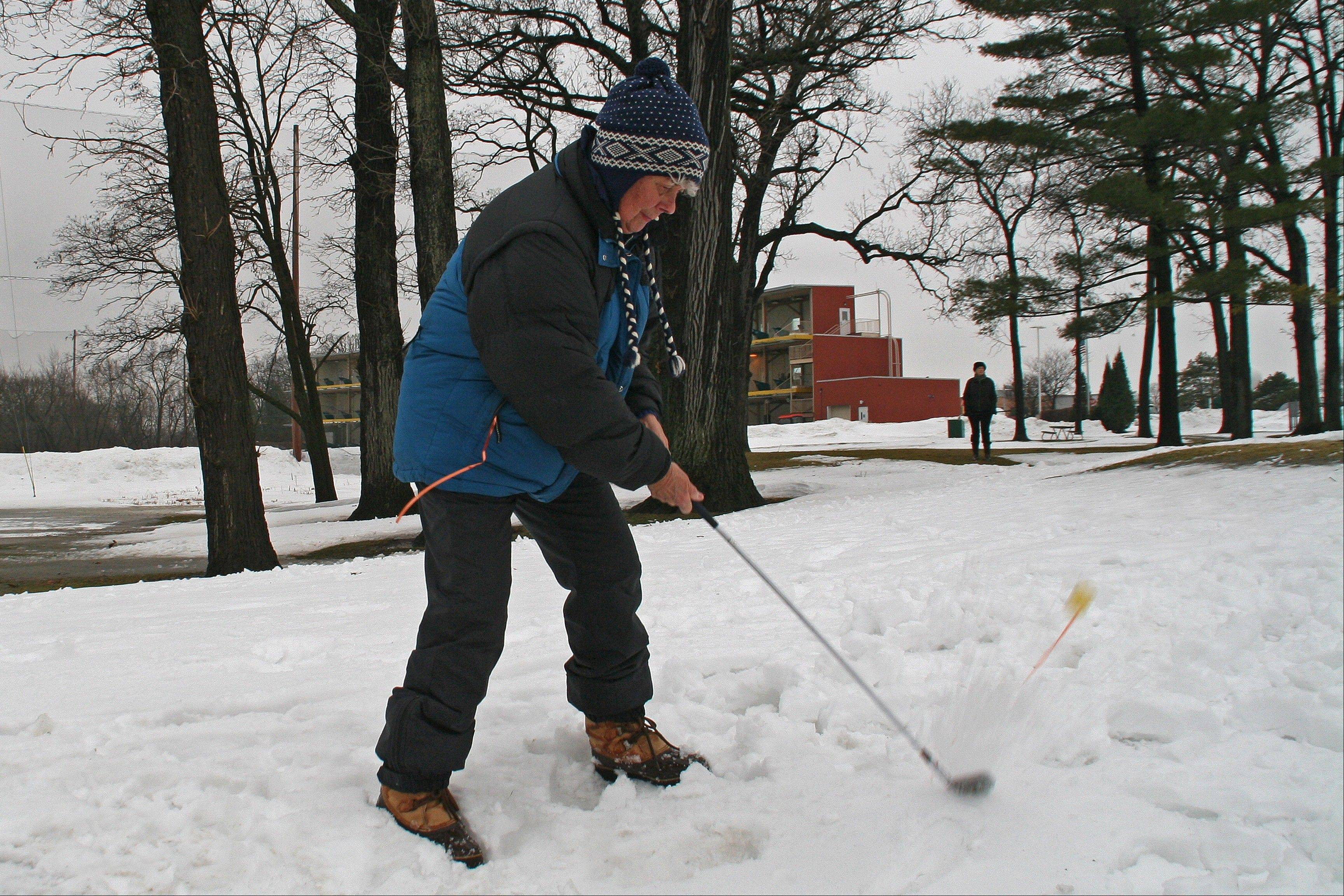 Marianne Balow pops her ball up and out of a snowdrift at the annual Des Plaines Park District Chili Open on Jan. 11, at the Golf Center Des Plaines. The yellow Srixon balls were drilled through and tied with orange curling ribbon to make them easier to find on the course.