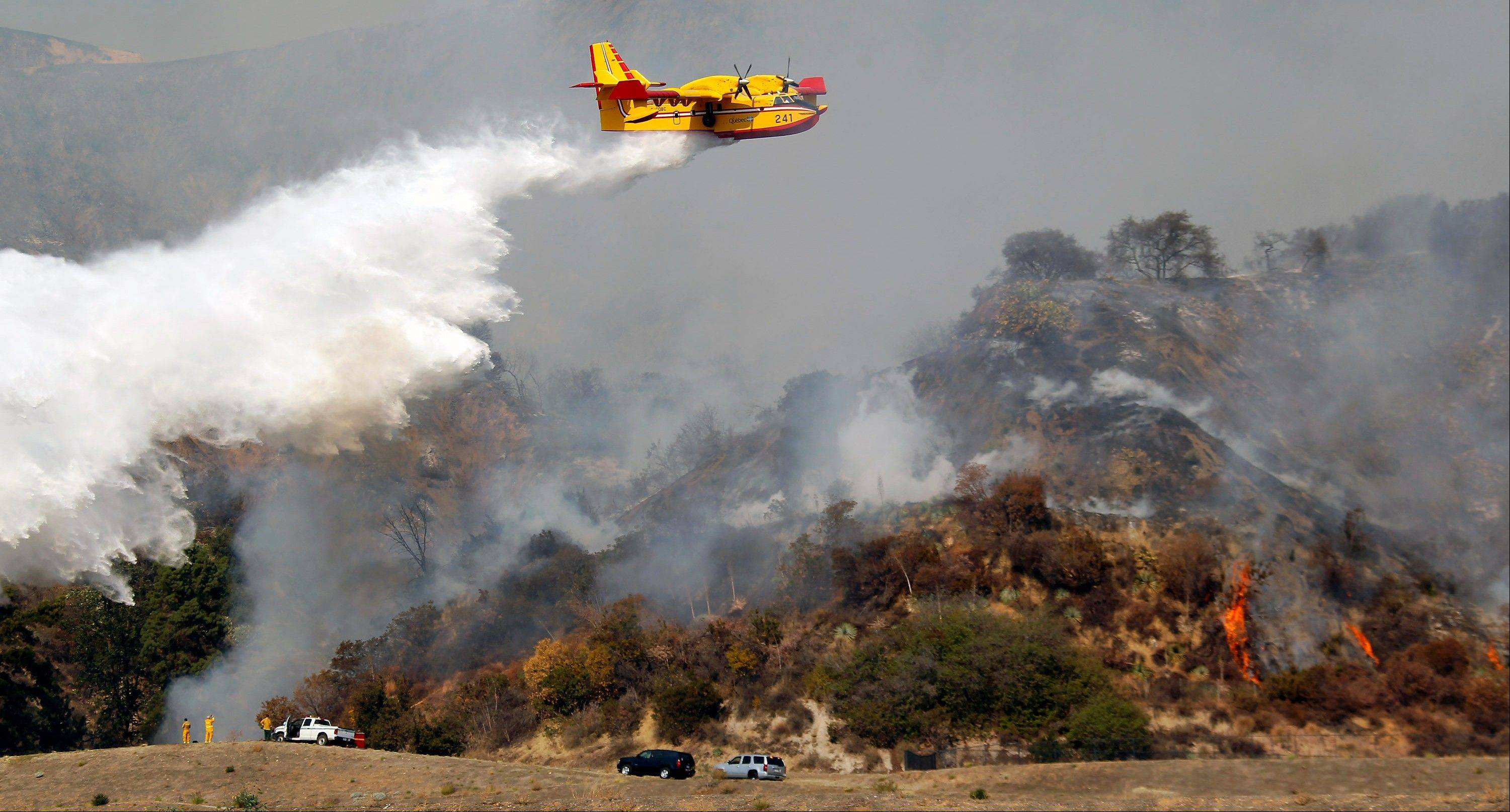 A firefighting plane makes a water drop on a wildfire that�s burning in the hills just north of the San Gabriel Valley community of Glendora, Calif., on Thursday, Jan 16, 2014. Southern California authorities have ordered the evacuation of homes at the edge of a fast-moving wildfire burning in the dangerously dry foothills of the San Gabriel Mountains.