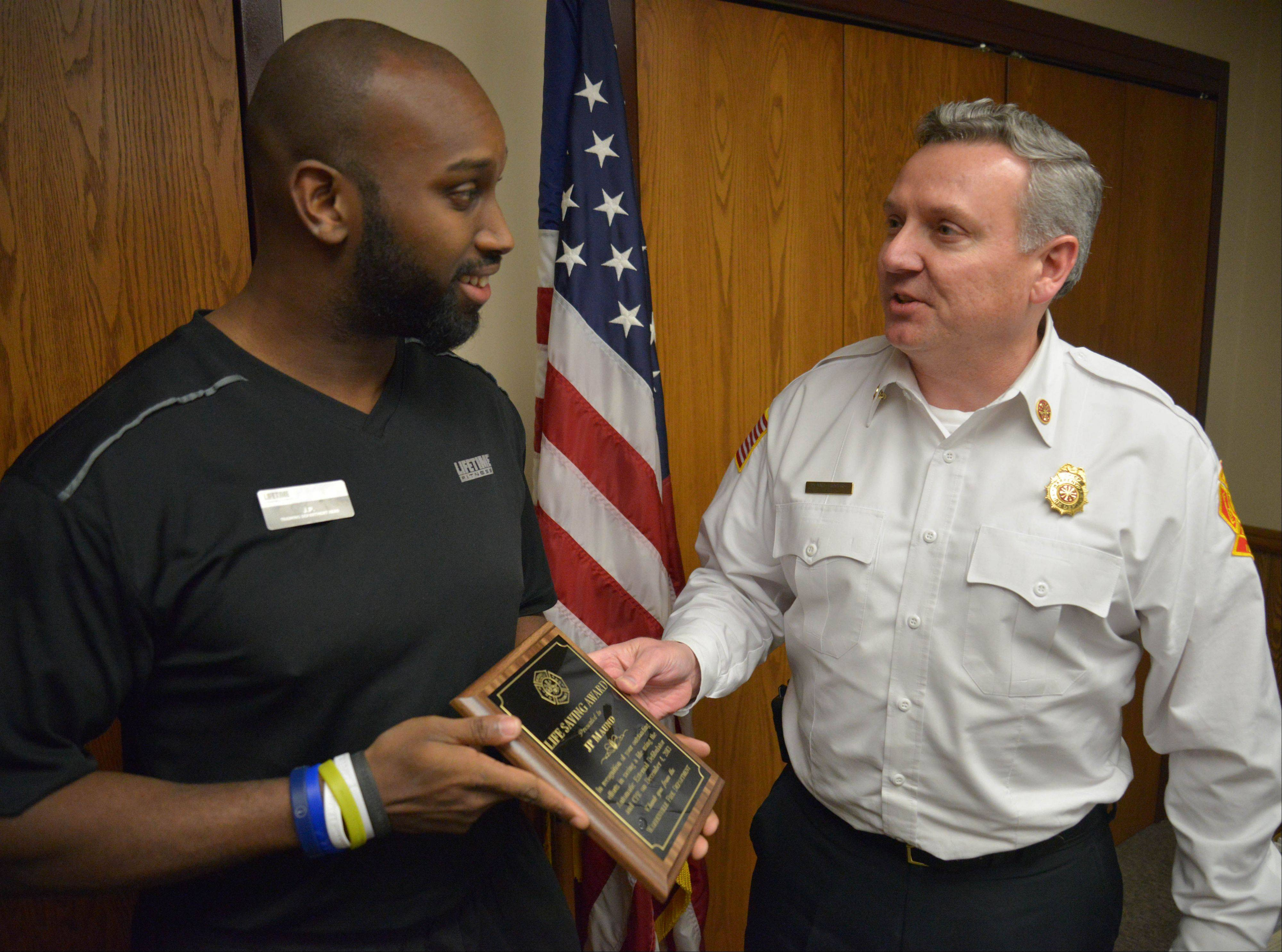 J.P. Maund, a trainer at Life Time Fitness in Warrenville, receives the Warrenville Fire Protection District's Lifesaving Award from Chief Dennis Rogers. Maund was honored Wednesday night for helping resuscitate a man who went into cardiac arrest at the gym Dec. 4.