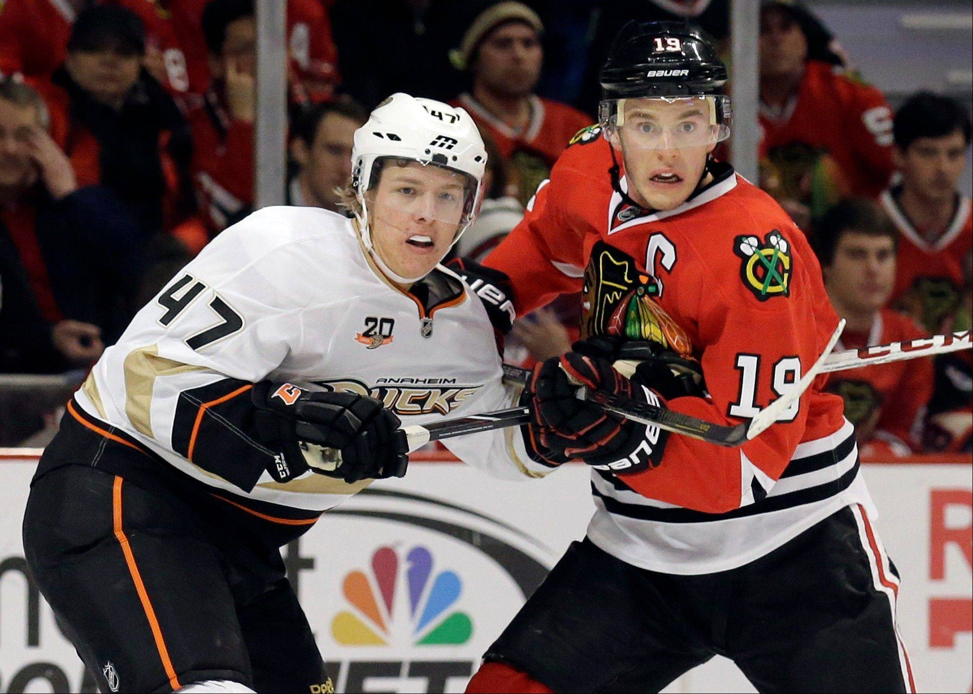 Chicago Blackhawks' Jonathan Toews, right, and Anaheim Ducks' Hampus Lindholm watch the puck during the second period of an NHL hockey game in Chicago, Friday, Jan. 17, 2014. (AP Photo/Nam Y. Huh)