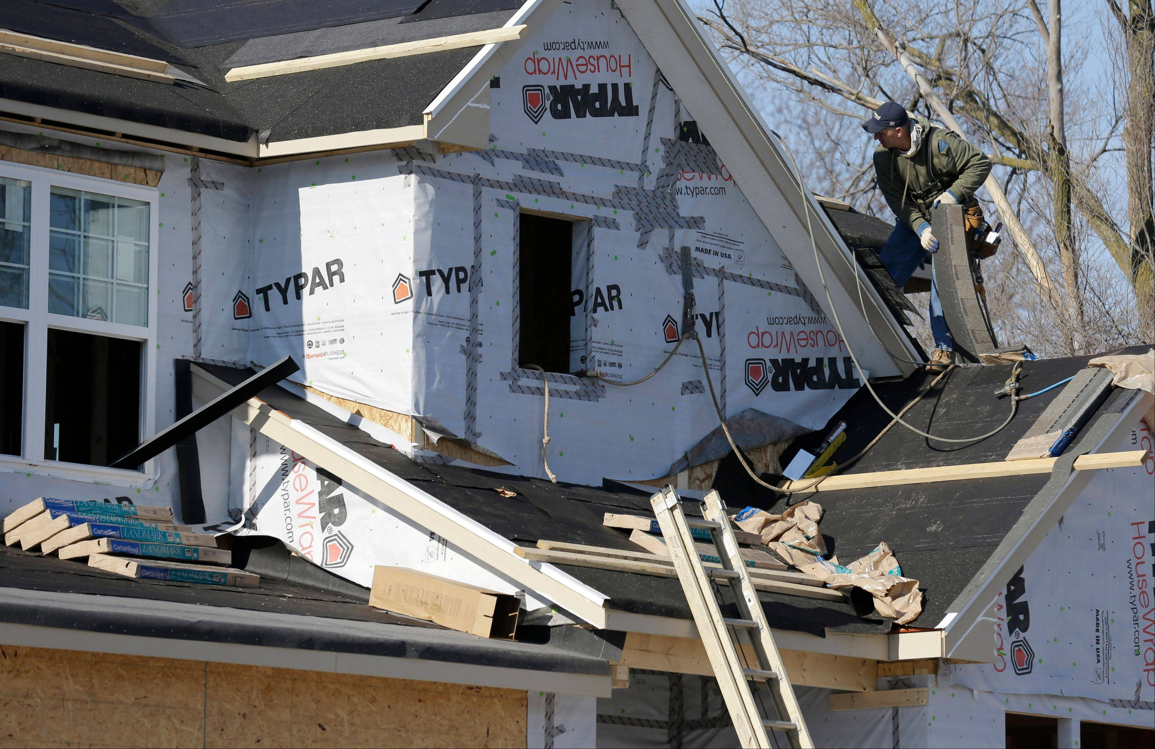 A builder works on the the roof of a home under construction in Wilmette last December.