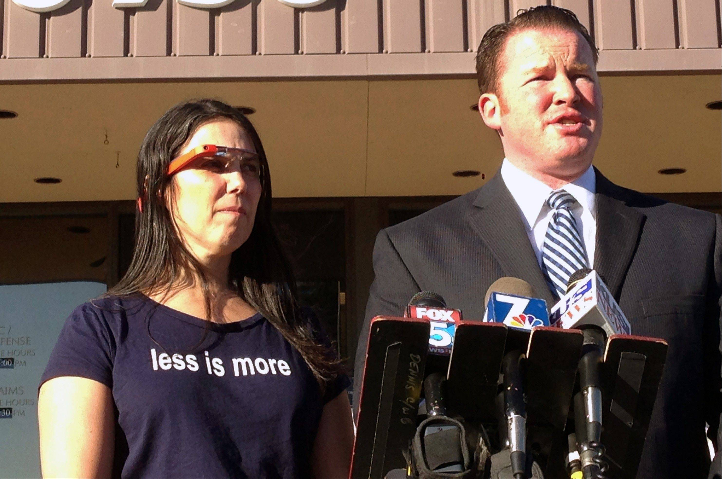 Cecilia Abadie, left, wears a Google Glass computer-in-eyeglass device while her attorney, William Concidine, speaks to the media, Thursday, Jan. 16, 2014 in San Diego. A San Diego traffic court threw out a citation Thursday against Abadie, a woman believed to be the first motorist in the country ticketed for driving while wearing a Google Glass computer-in-eyeglass device.