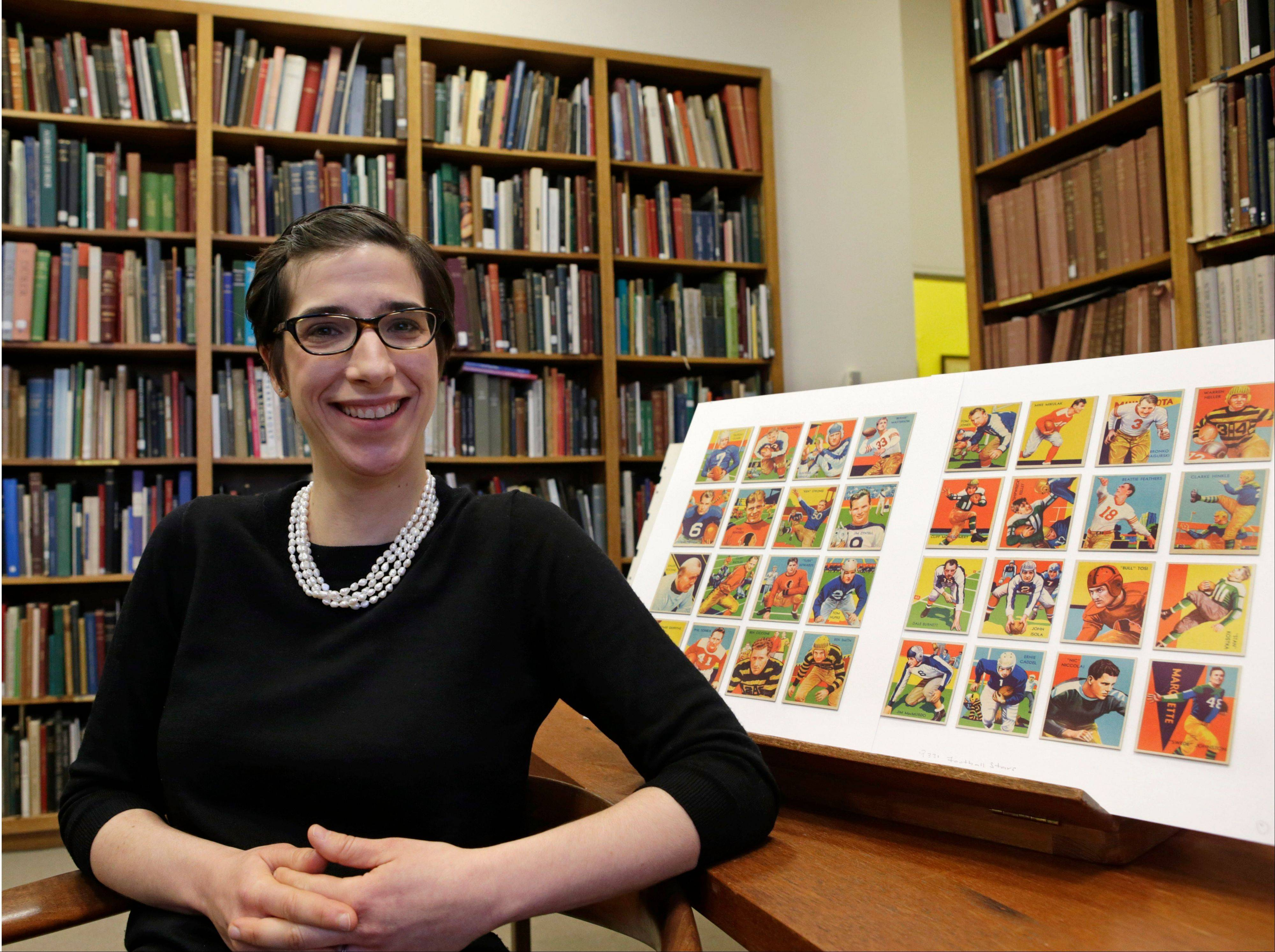 "Assistant curator Freyda Spira, of the department of drawings and prints at the Metropolitan Museum of Art in New York, shows some of the football cards that are part of the ""Gridiron Greats"" exhibition that runs Jan. 24 through Feb. 10."