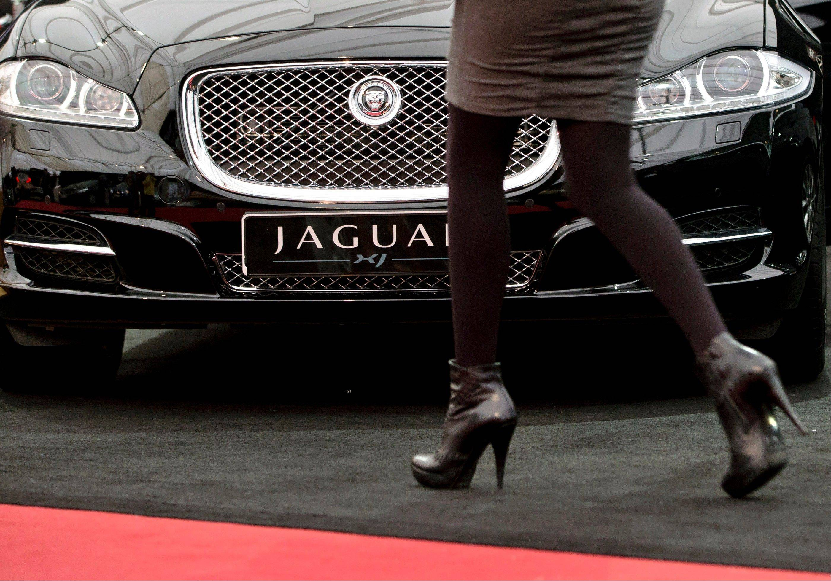A woman passes by a Jaguar XJ during an Auto Moto Show in Bucharest, Romania. Women now buy nearly half the new cars in the U.S.