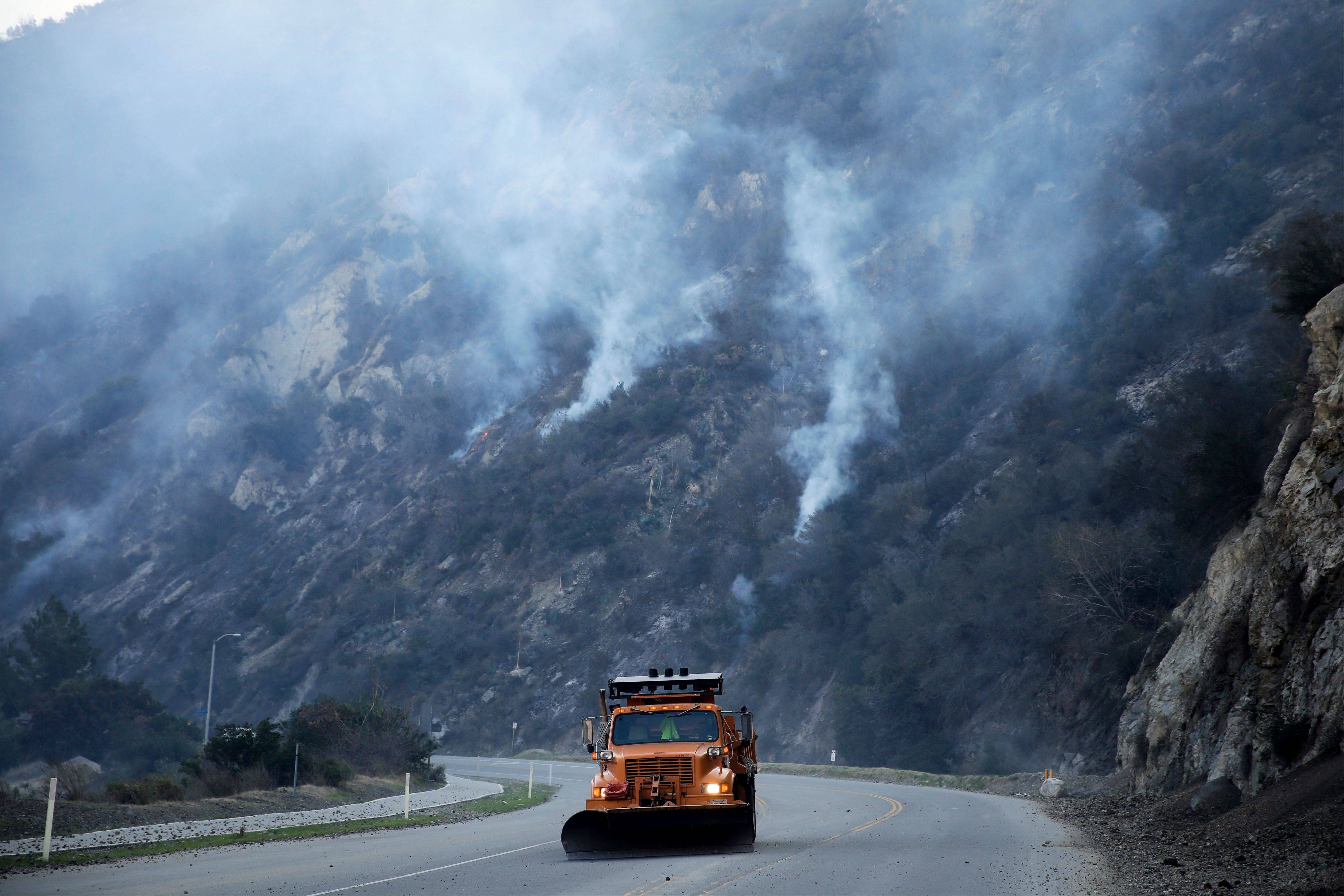A truck clears away rocks along San Gabriel Canyon Road as firefighters continue Friday to battle the Colby Fire.
