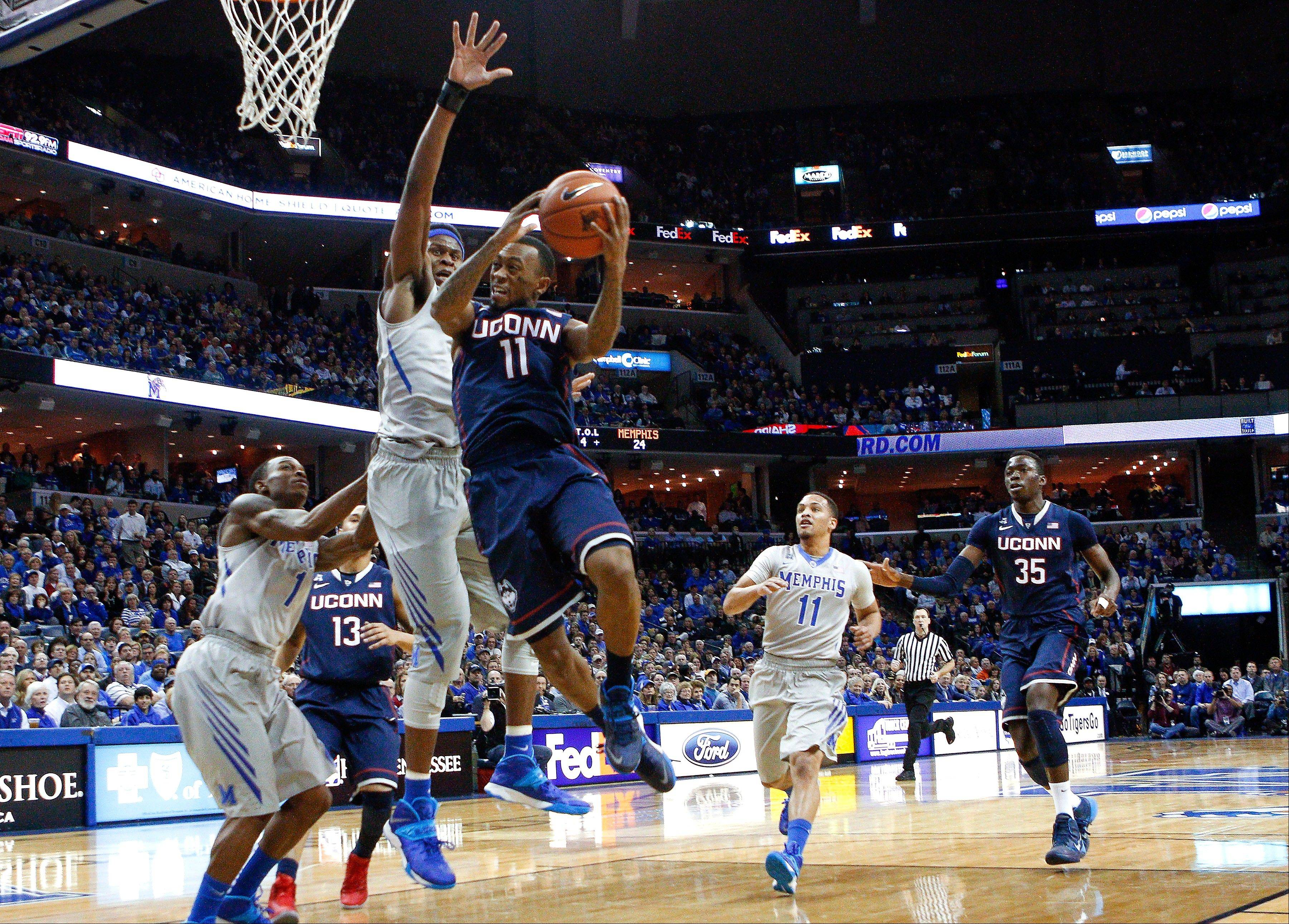 Connecticut guard Ryan Boatright, an Aurora native, goes to the basket against Memphis defenders Joe Jackson, left, and David Pellom in the first half of Thursday's game in Memphis, Tenn.