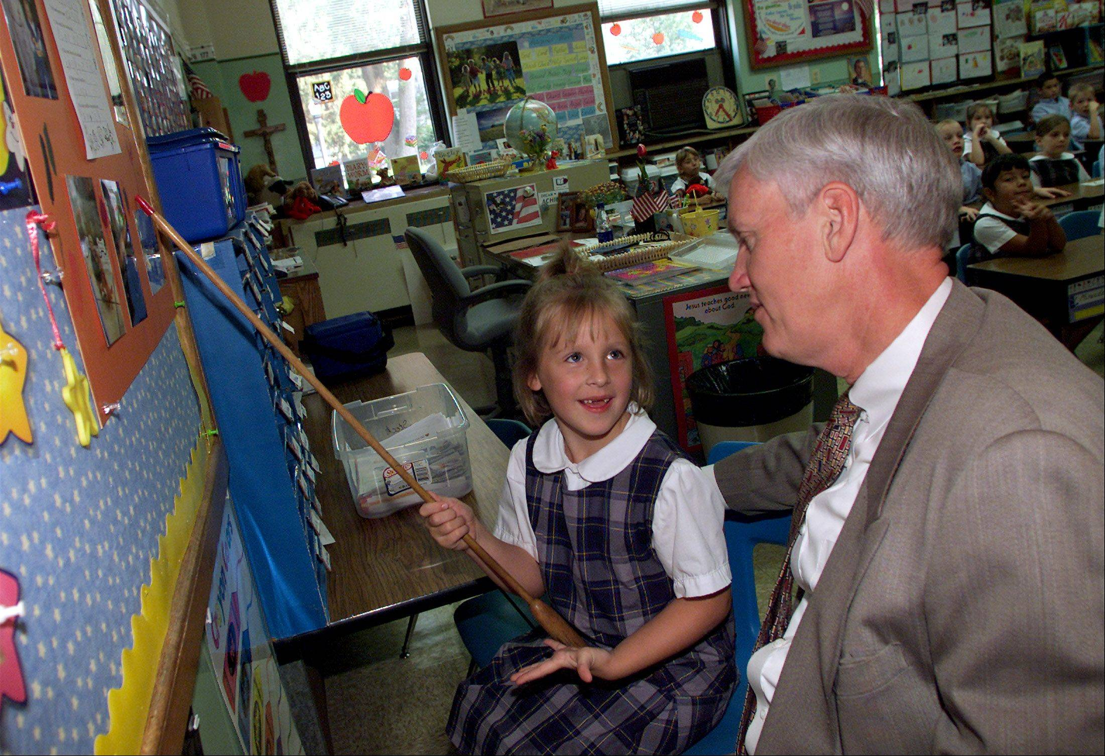 Longtime Ss. Peter and Paul School Principal Frank Glowaty hears a presentation from a student in this 2003 photo. Glowaty announced Thursday night that he will retire at the end of this school year after 39 years as principal at the school affiliated with Naperville's oldest Catholic church.