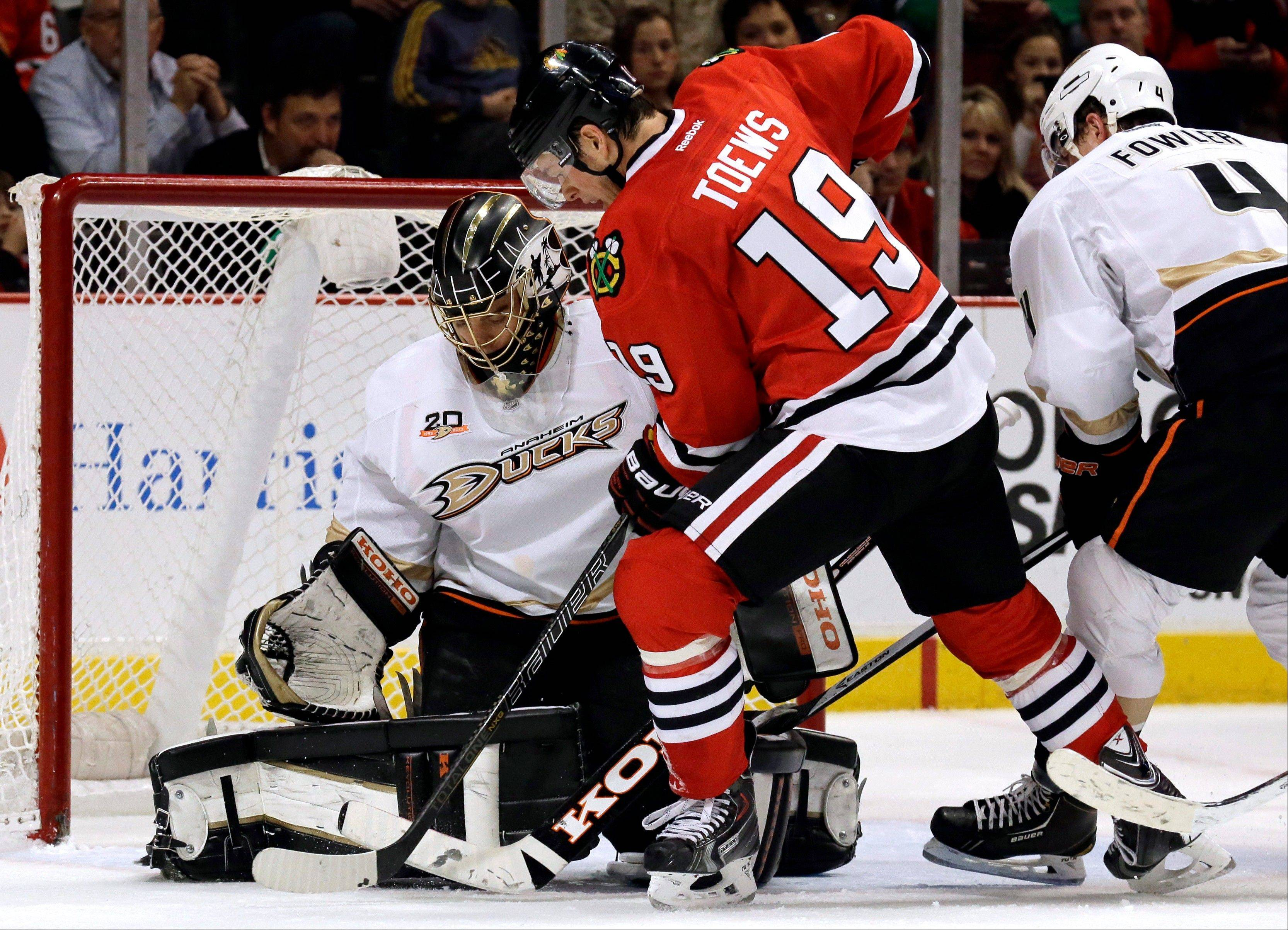 The Blackhawks' Jonathan Toews puts pressure on Ducks goalie Jonas Hiller during the second period Friday at the United Center.