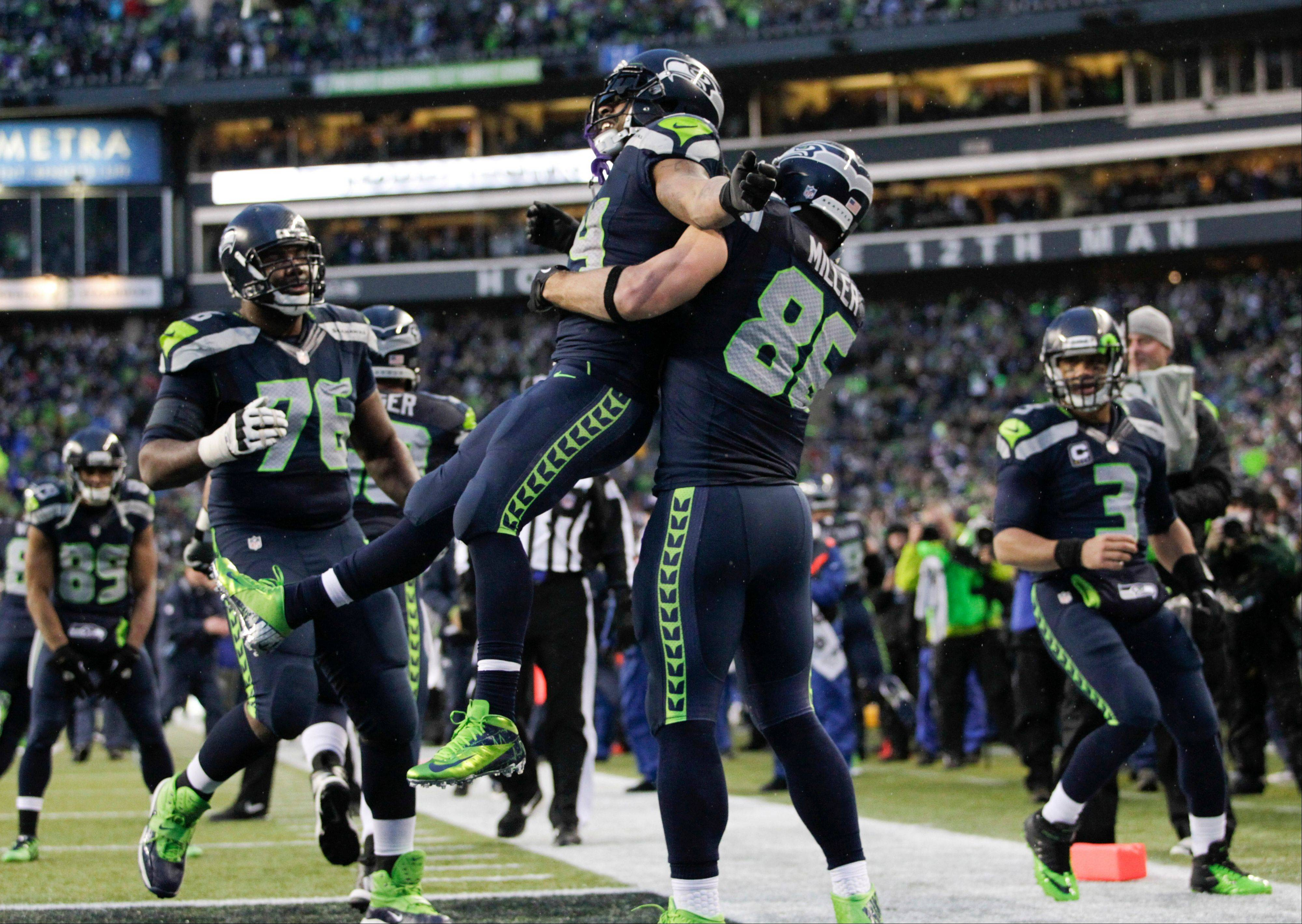 Seattle Seahawks running back Marshawn Lynch (24) celebrates with tight end Zach Miller (86) after running for a 31-yard touchdown against the New Orleans Saints during the fourth quarter of an NFC divisional playoff NFL football game in Seattle, Saturday, Jan. 11, 2014.
