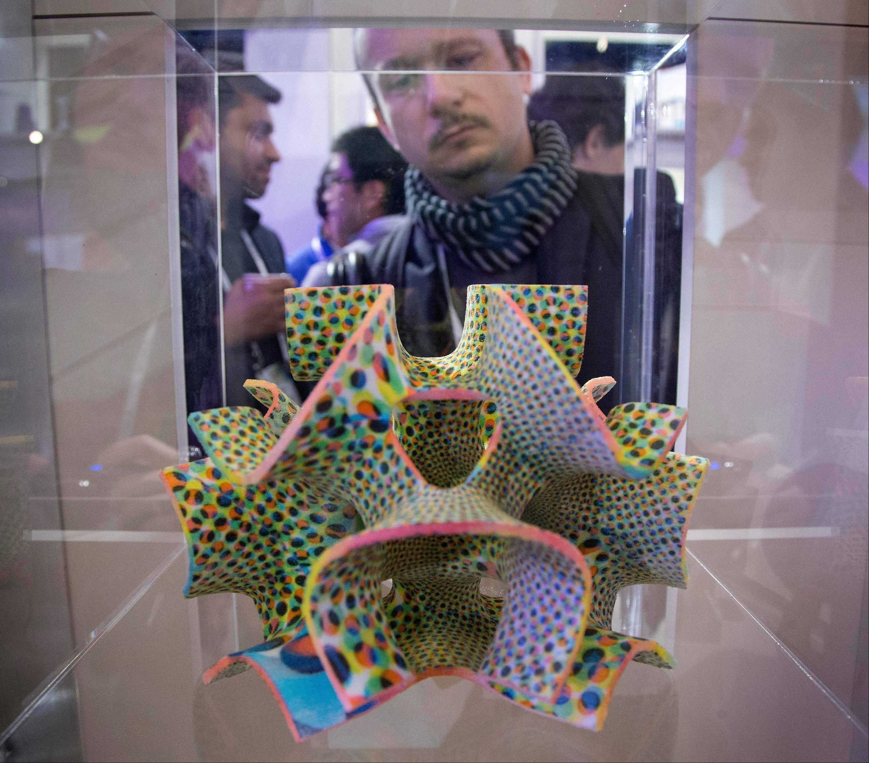 A trade show attendee examines a centerpiece confection made with a ChefJet Pro 3-D food printer on display at the International Consumer Electronics Show.