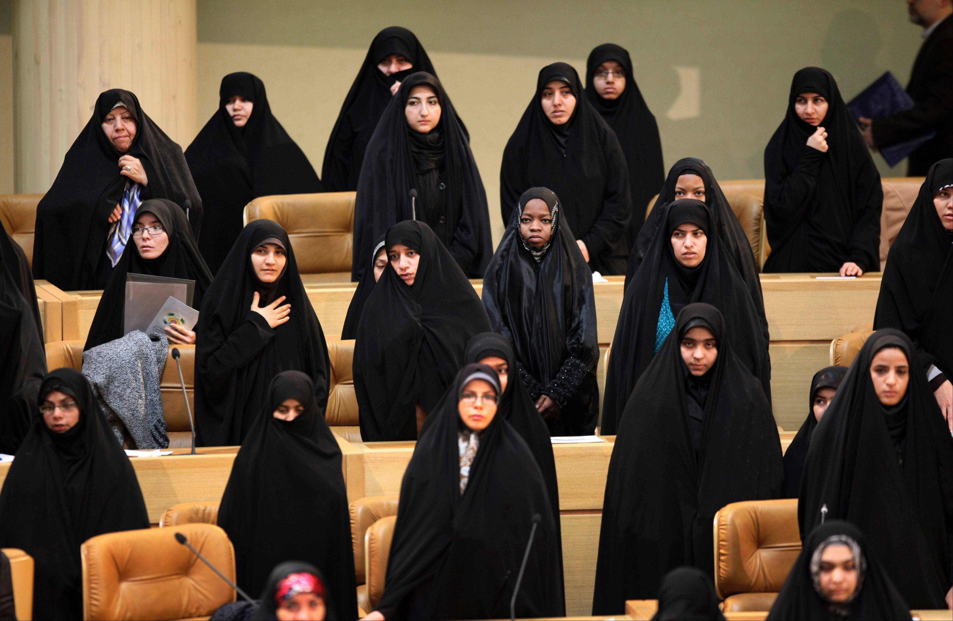 Female participants of the 27th International Islamic Unity Conference stand Friday as they listen to the Iranian national anthem in Tehran.
