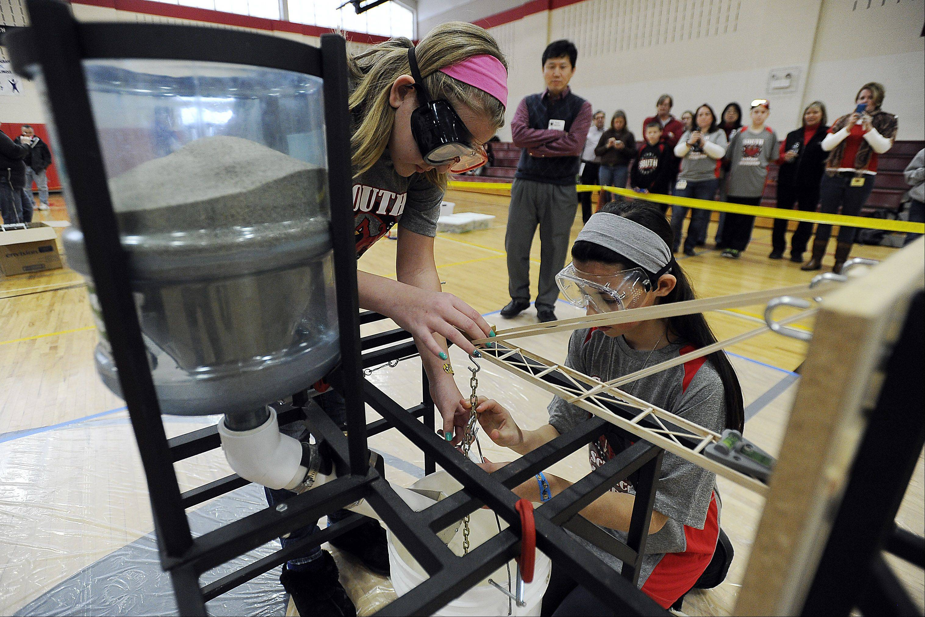 Avery Hepko, 11, left, and partner Elizabeth Ibata, 12, of South Middle School in Arlington Heights hook up their wooden boom structure device to a bucket that will fill with sand. Supervisor Yongjian Liu watches carefully as the girls prepare their device at a Science Olympiad invitational. The boom held more than 22 pounds of sand.