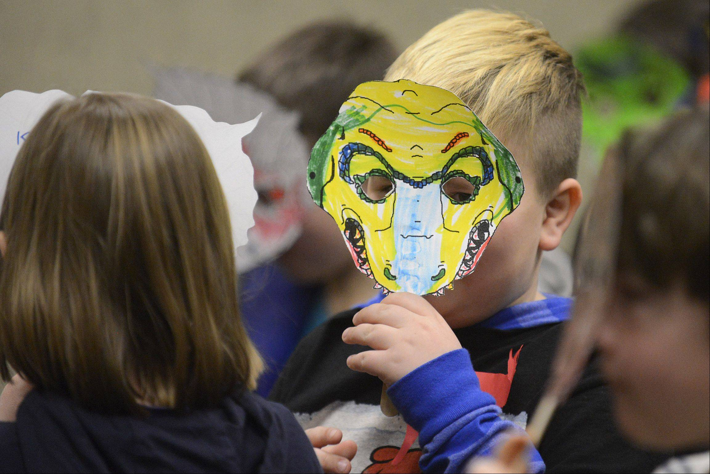 Gavin Harrison, 6, of Algonquin peers from behind the T-Rex mask he colored during the dinosaur themed Super Saturday program at Algonquin Public Library on Saturday. The once-a-month program is for kindergarten and first graders who hold a Algonquin library card.