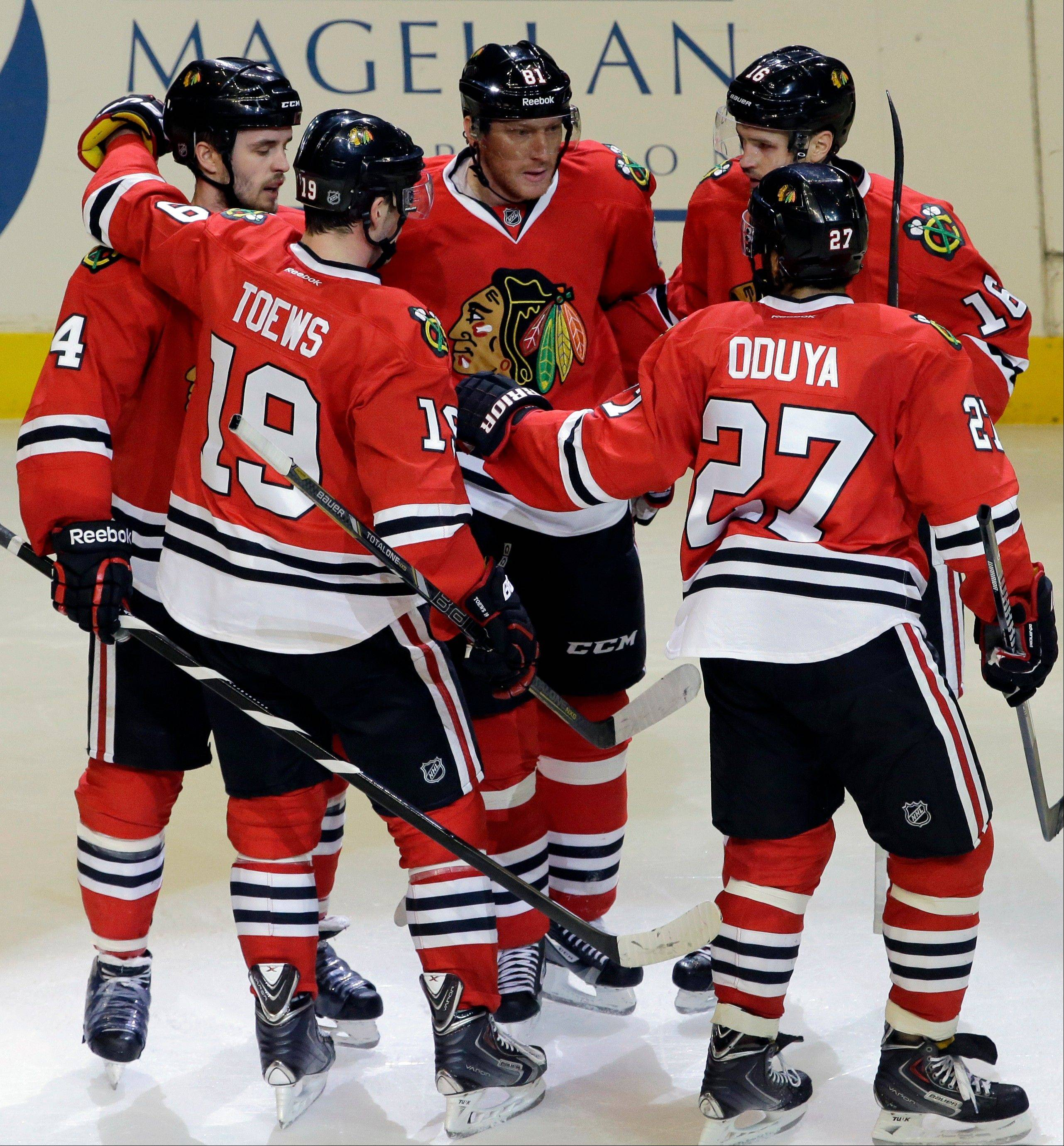 The Blackhawks� Marian Hossa, middle, celebrates with teammates after scoring his second goal during Friday�s victory over Anaheim at the United Center.