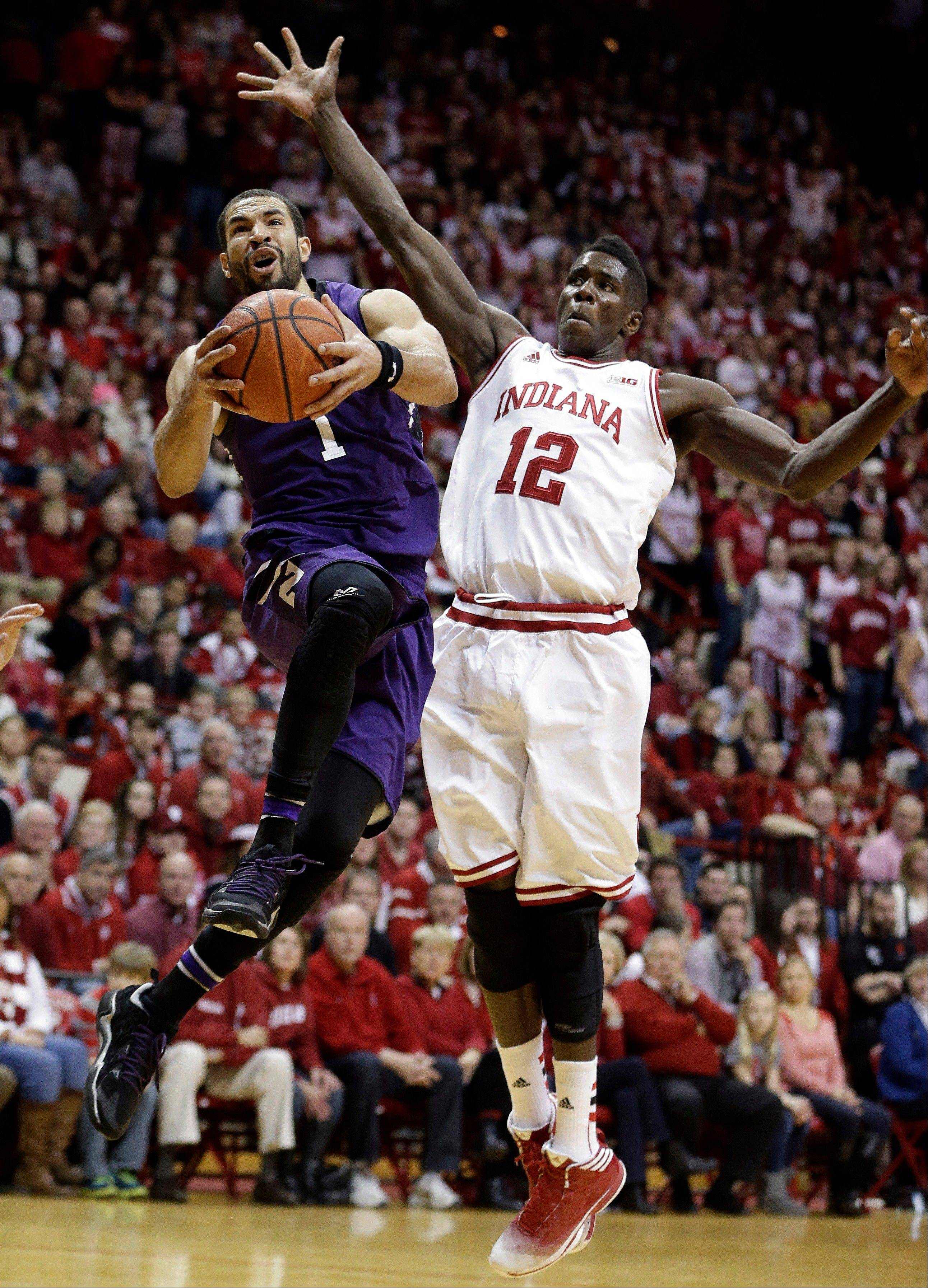 Northwestern's Drew Crawford (1) put up a shot against Indiana's Hanner Mosquera-Perea (12) during the first half of an NCAA college basketball game Saturday, Jan. 18, 2014, in Bloomington, Ind. (AP Photo/Darron Cummings)
