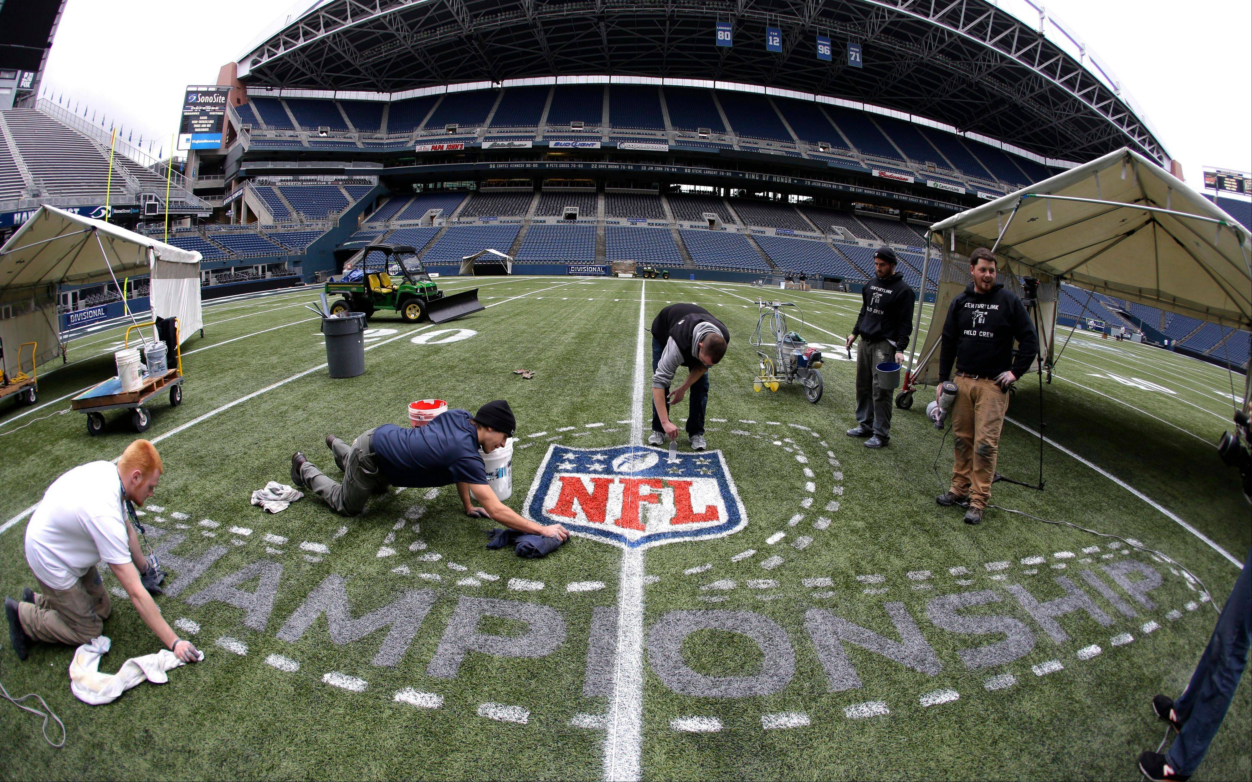 In this photo made with a fisheye lens, members of the CenturyLink Field stadium operations team paint an NFL championship logo Tuesday, Jan. 14, 2014, as they prepare the field for Sunday's NFL football NFC championship game between the Seattle Seahawks and the San Francisco 49ers. (AP Photo/Ted S. Warren)