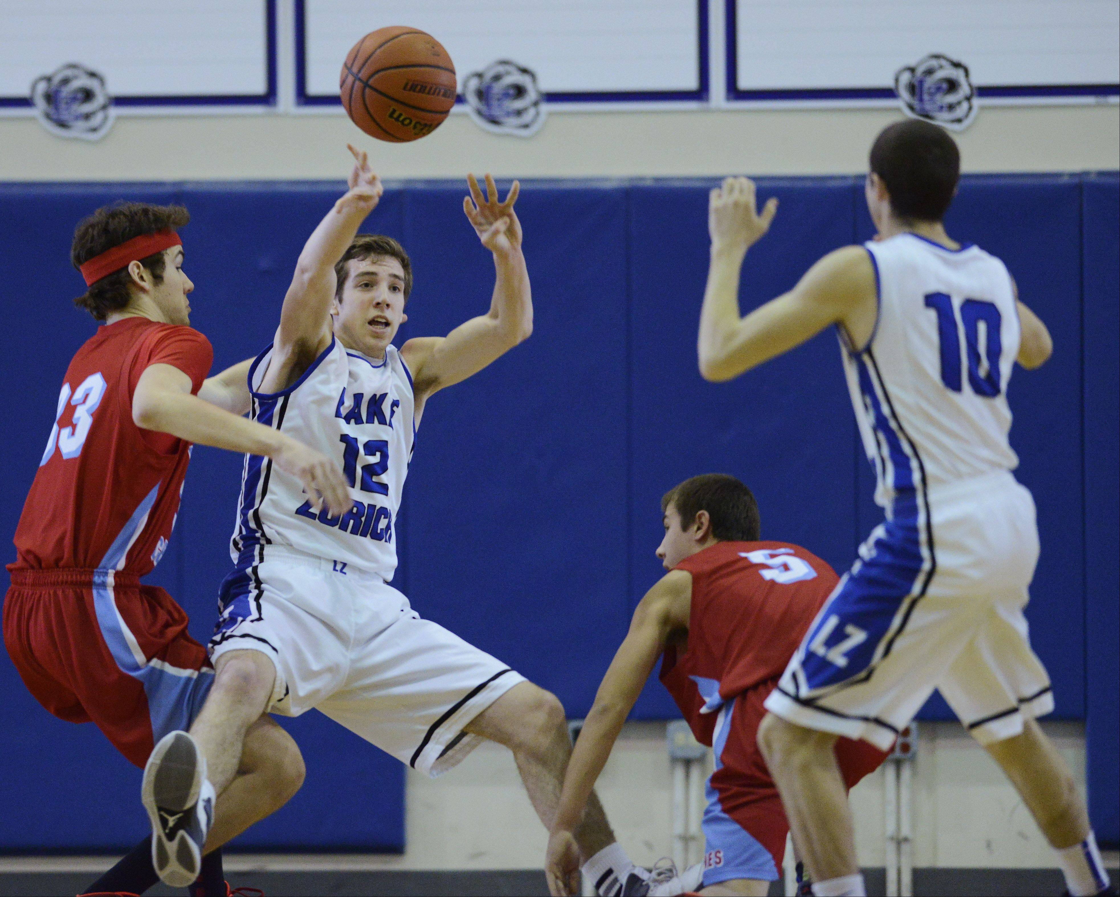 Lake Zurich�s Corey Helgeson, second from left, passes the ball to teammate Dave Brown, right, after grabbing a loose ball between Marian Central�s Quinn Haley, left, and Adam Pischke during the Martin Luther King Classic at Lake Zurich Saturday.