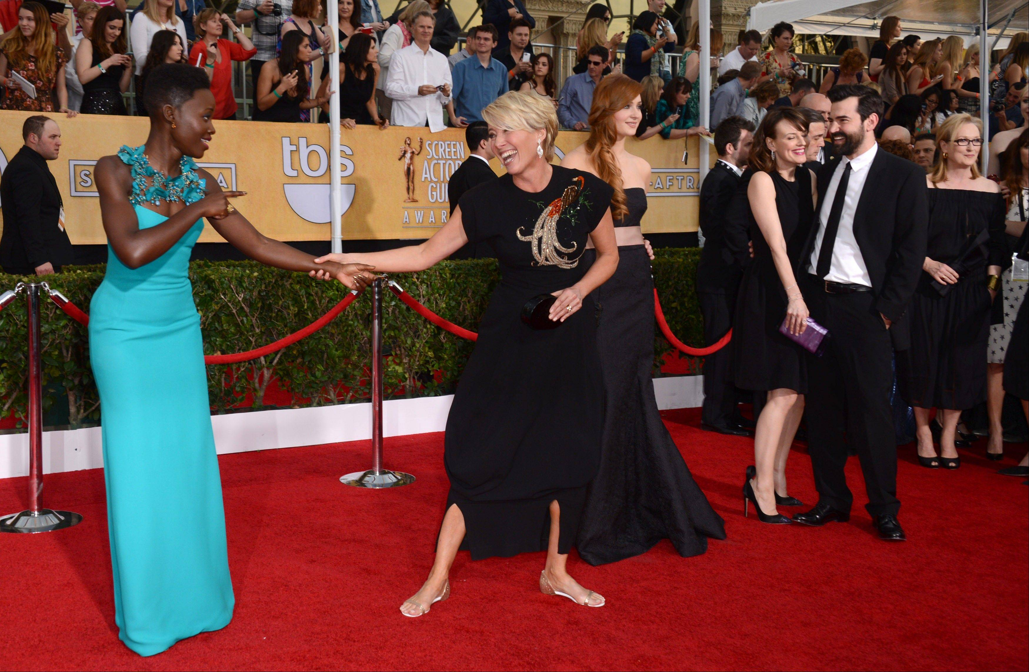 Actresses Lupita Nyong'o, left, and Emma Thompson greet one another on the SAG Awards red carpet.