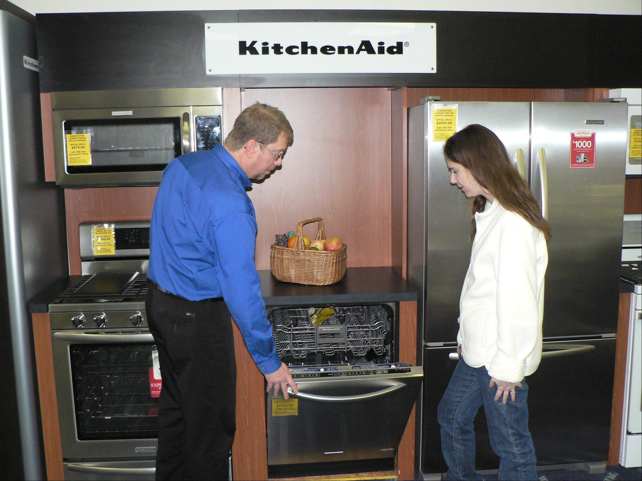 Salesman Don Ellison shows Lisa Swan of Bartlett a Kitchen Aid suite of appliances at Schaumburg's Advanced Maytag.