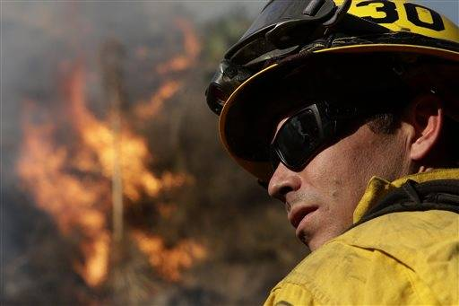 Firefighter Jeff Newby watches a fire burn as he battles the Colby Fire on Friday, Jan. 17, 2014, near Azusa, Calif. Firefighters were chasing flare-ups Friday morning in the damaging wildfire that was largely tamed but kept thousands of people from their homes in the foothill suburbs northeast of Los Angeles.