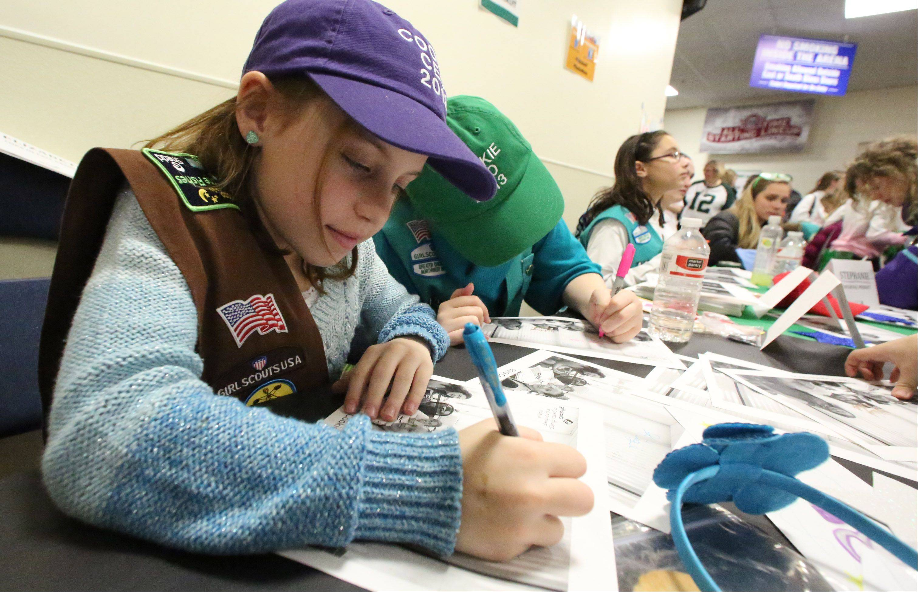 Gianna Girup, 9, of Wheaton, signs autographs at the fifth annual Girl Scouts Cookie Kickoff Rally. She earned the title of Chicago area Girl Scout cookie sales CEO for selling 2,434 boxes in 2013.