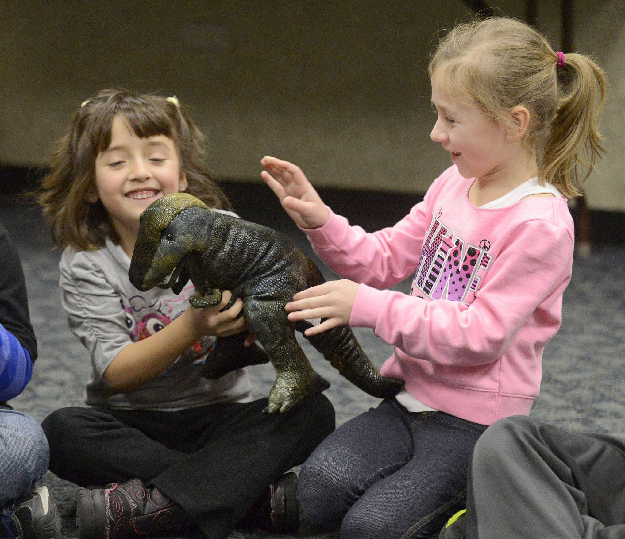 Carla Llorente, 5, is tossed a T-Rex puppet by friend Gabriella Wojtarowicz, 6, during a game of hot dinosaur (like hot potato) during a dinosaur themed Super Saturday program at Algonquin Public Library on Saturday, January 18. Both girls are from Algonquin and attend programs at the library often.