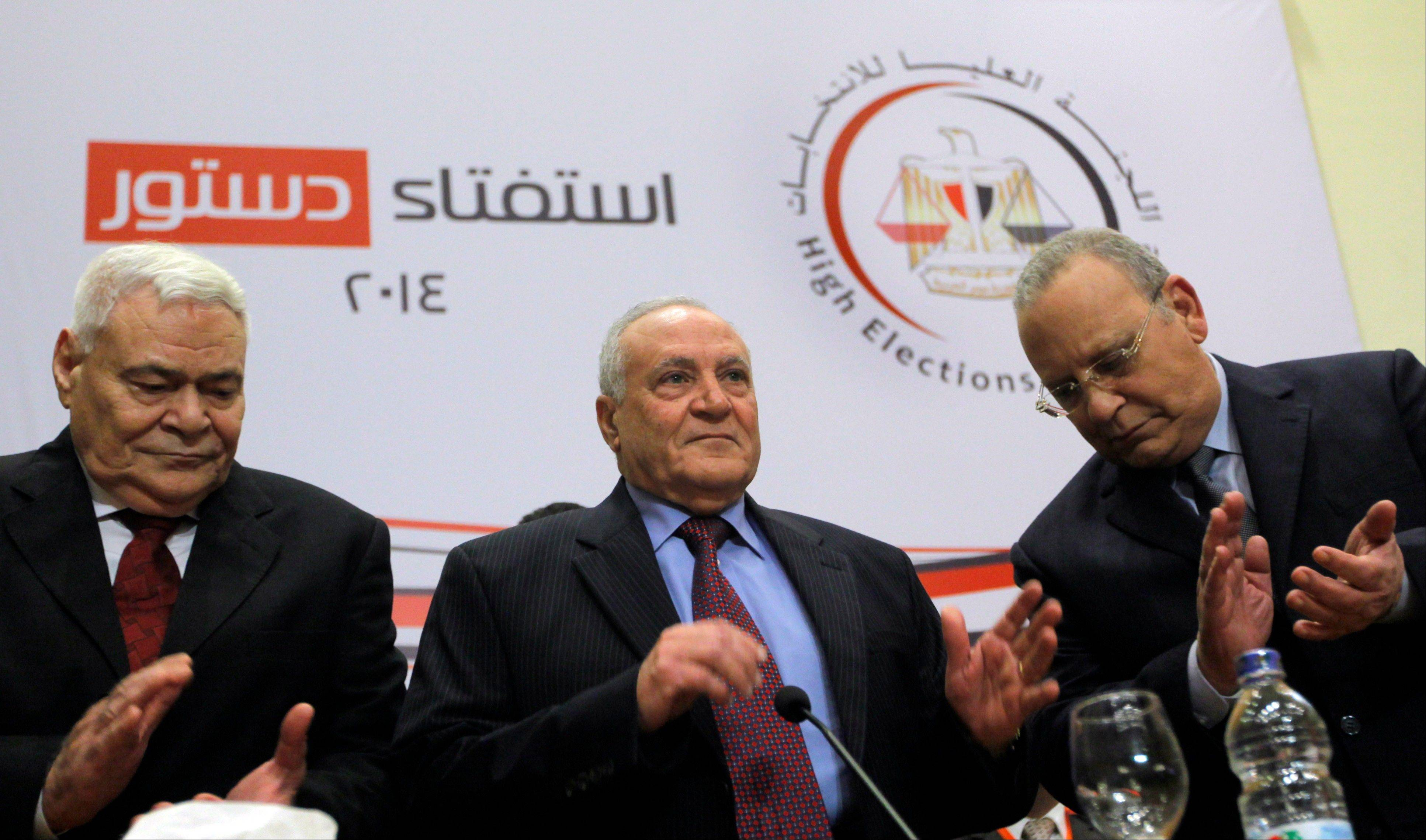 Judge Nabil Salib, head of Egypt's High Election Commission, center, is greeted by other members as he prepares to announce the voting results Saturday of a referendum on Egypt's military-backed constitution, in Cairo, Egypt.