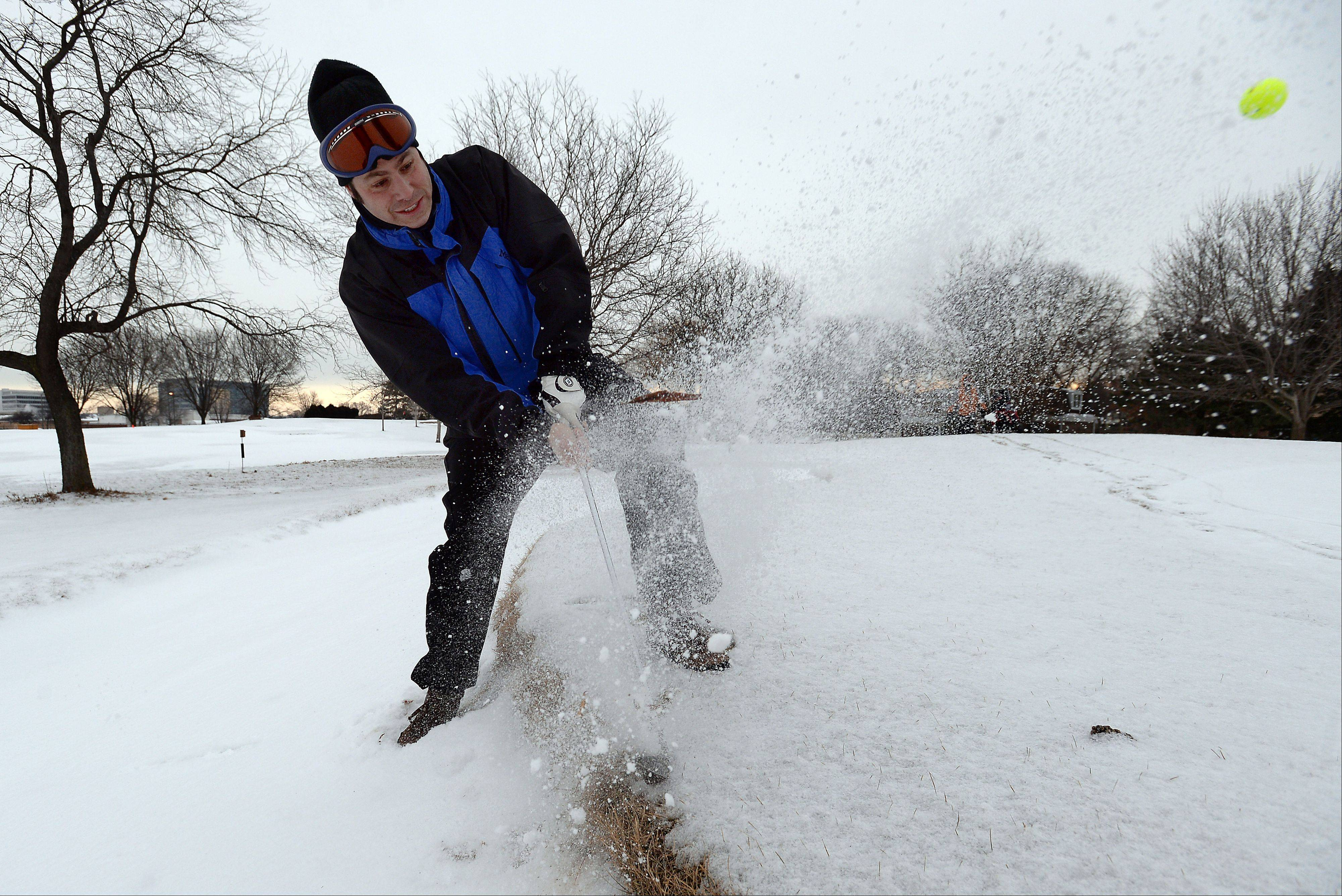 "Harlan Heiber of Arlington Heights struggles to chip out of the frozen snow trap on the 10th hole during the 2014 Chilly Open at Arlington Lakes Golf Club on Saturday. Heiber, who has been doing this for eight years, says, ""It's fun to say that you golfed last week in a foot of snow."""
