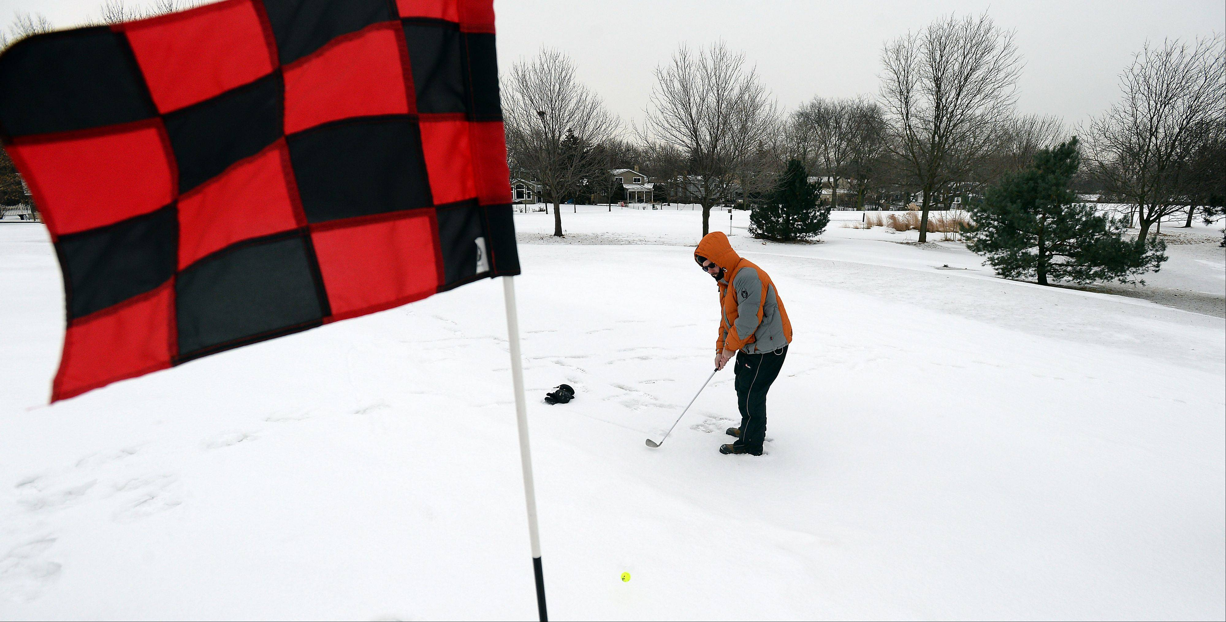 Willie Mills of Roselle chips up from the frozen ground on the 10th hole during the 2014 Chilly Open at Arlington Lakes Golf Club on Saturday.