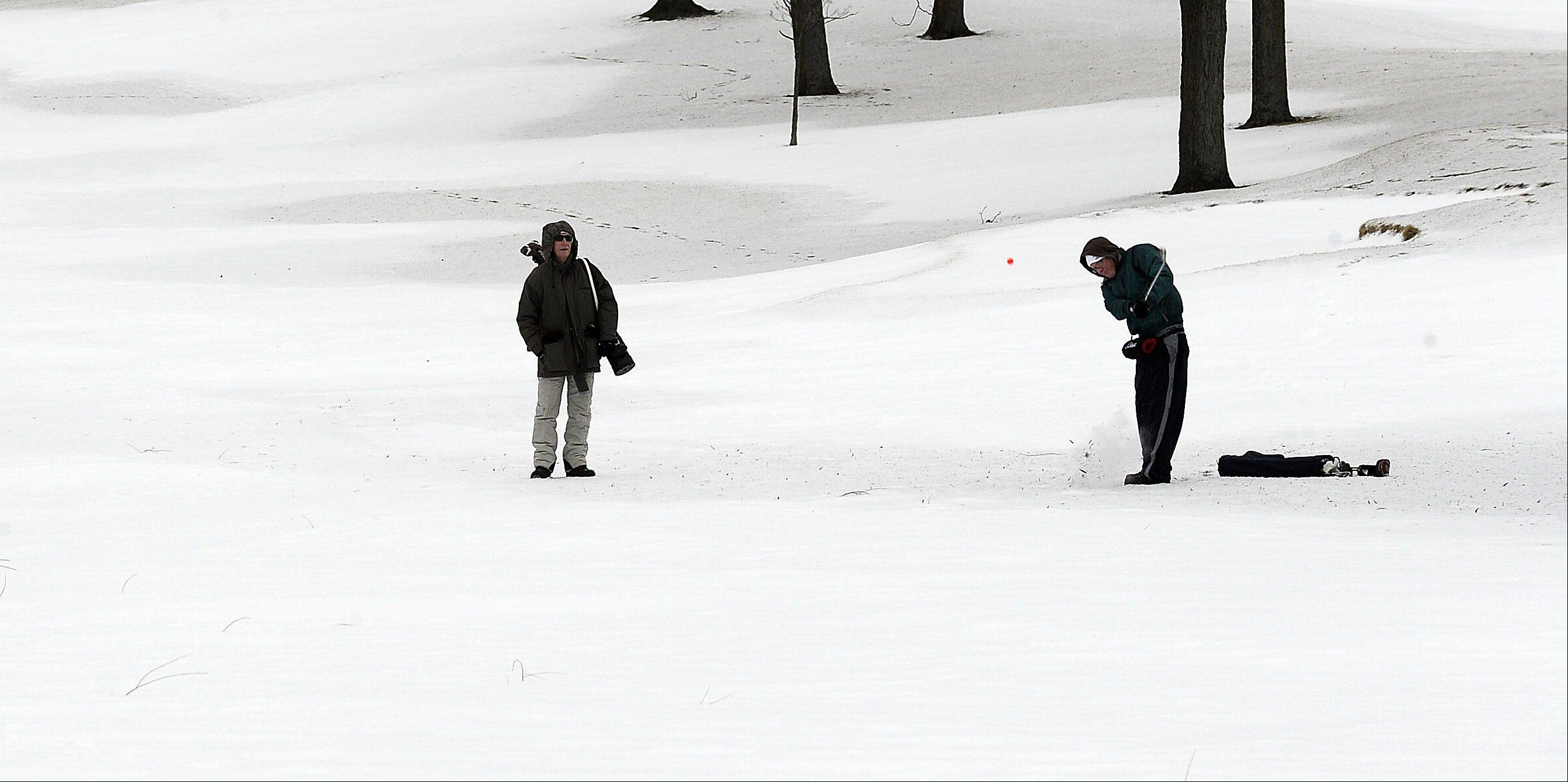 "Kurt Johnson of Arlington Heights hits his chip shot up from the snow to the 10th hole as his buddy Burt Wiekert of Kentucky looks on during the 2014 Chilly Open at Arlington Lakes Golf Club on Saturday. Johnson says ""It's fun -- don't get to golf in January very often."""