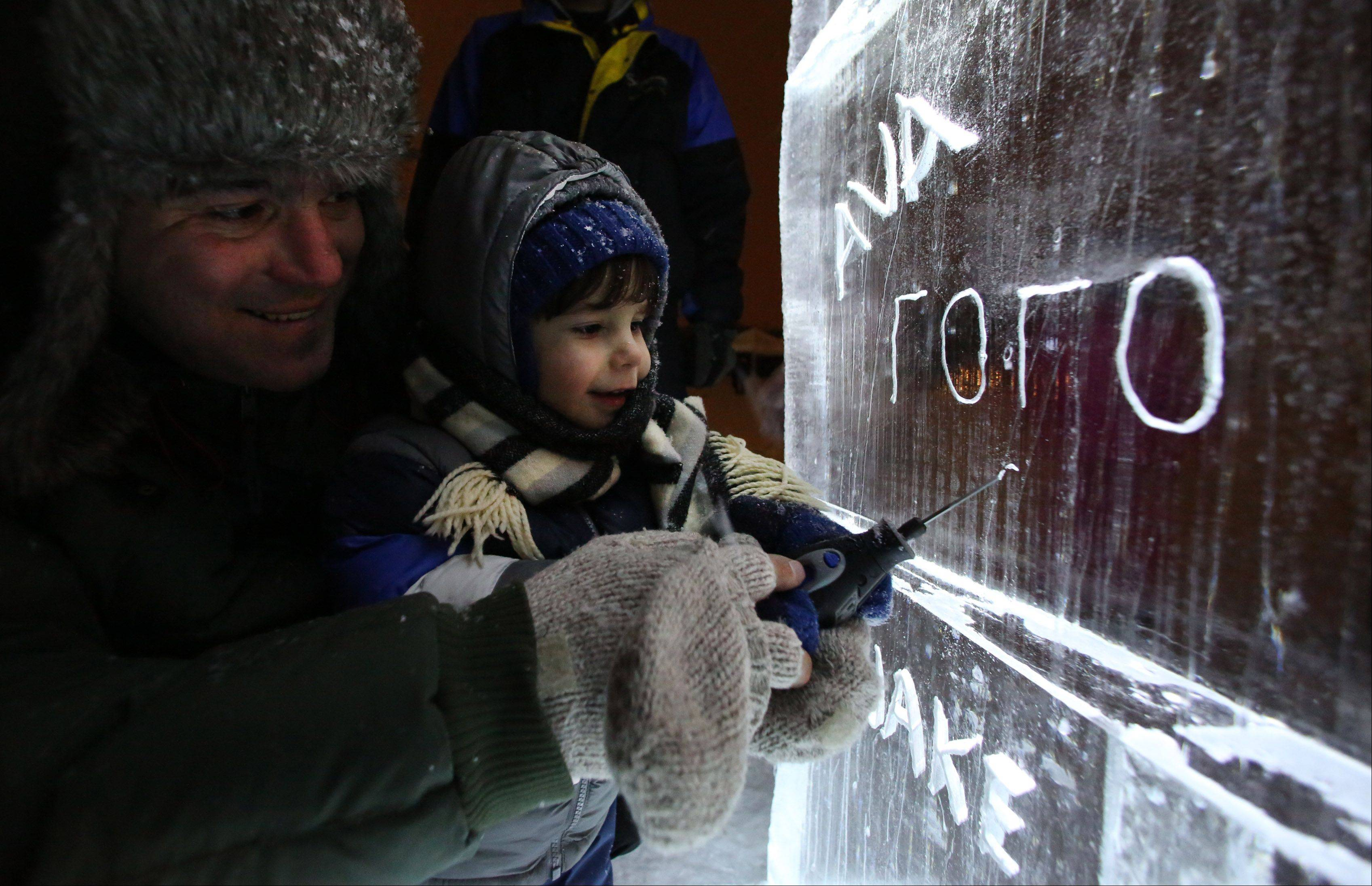 Two-year-old George Encher of Gurnee starts to carve his name in a large ice block while being held by his dad, also named George, on Friday night at the Gurnee Park District's annual Frosty Fest.
