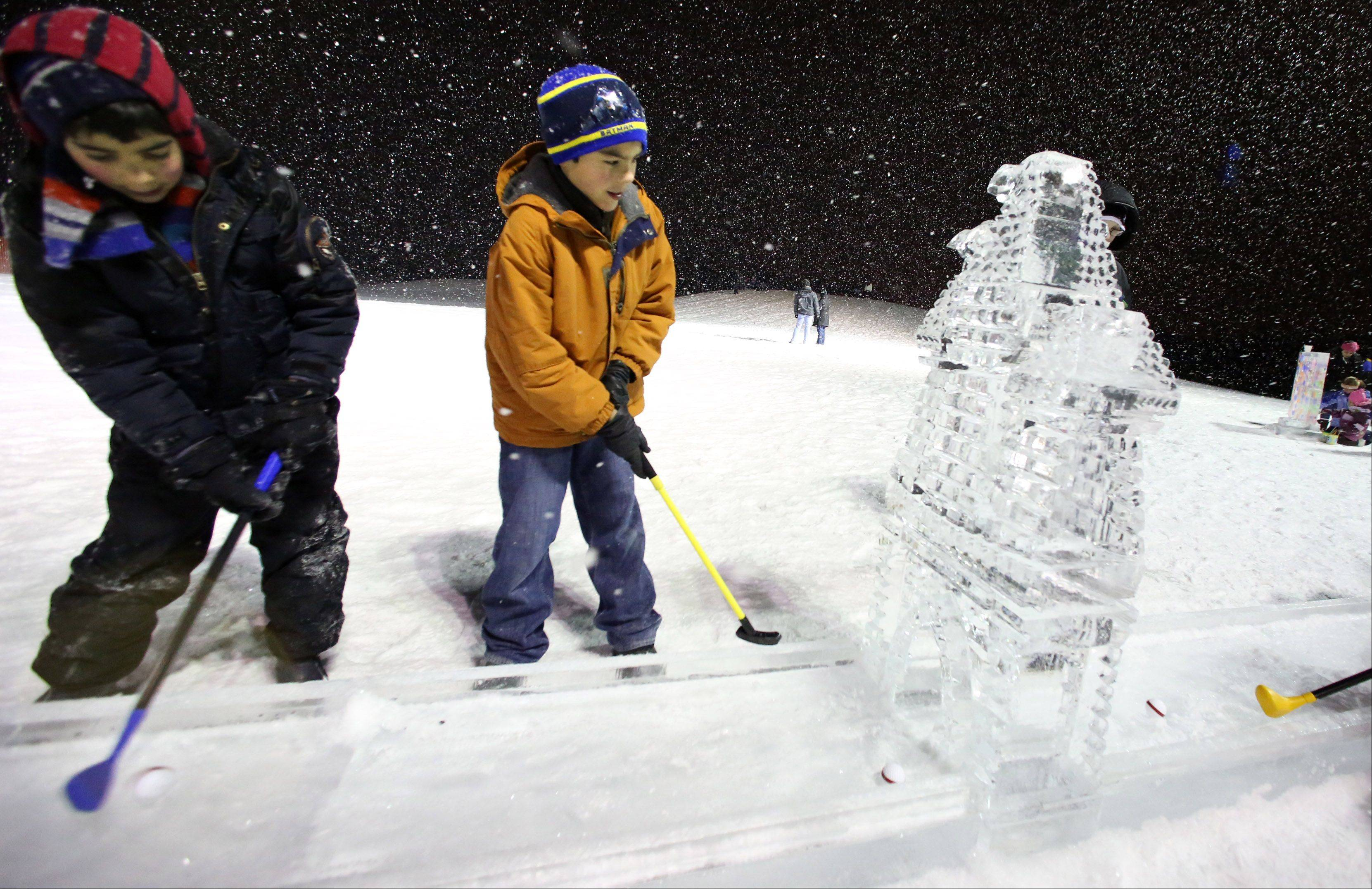 Brothers Luis, 10, left, and Alan Contreras, 9, play golf on a miniature ice golf course at Gurnee Park District't annual Frosty Fest on Friday night at Bittersweet Golf Course in Gurnee.