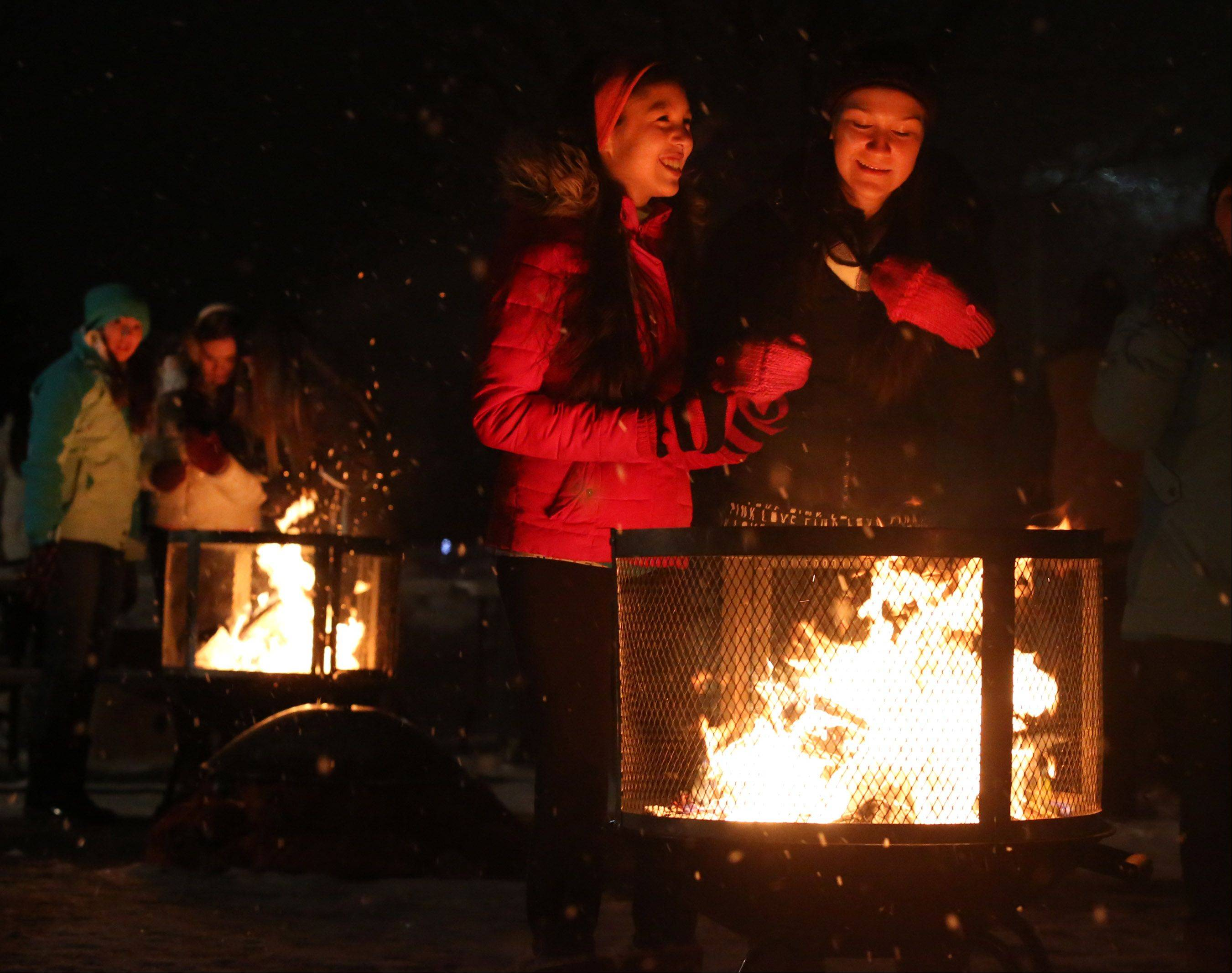 Hannah Hansen and friend Chelsea Tillman, both 14 of Gurnee, keep warm at one of three fire pits at the Frosty Fest on Friday night in Gurnee.