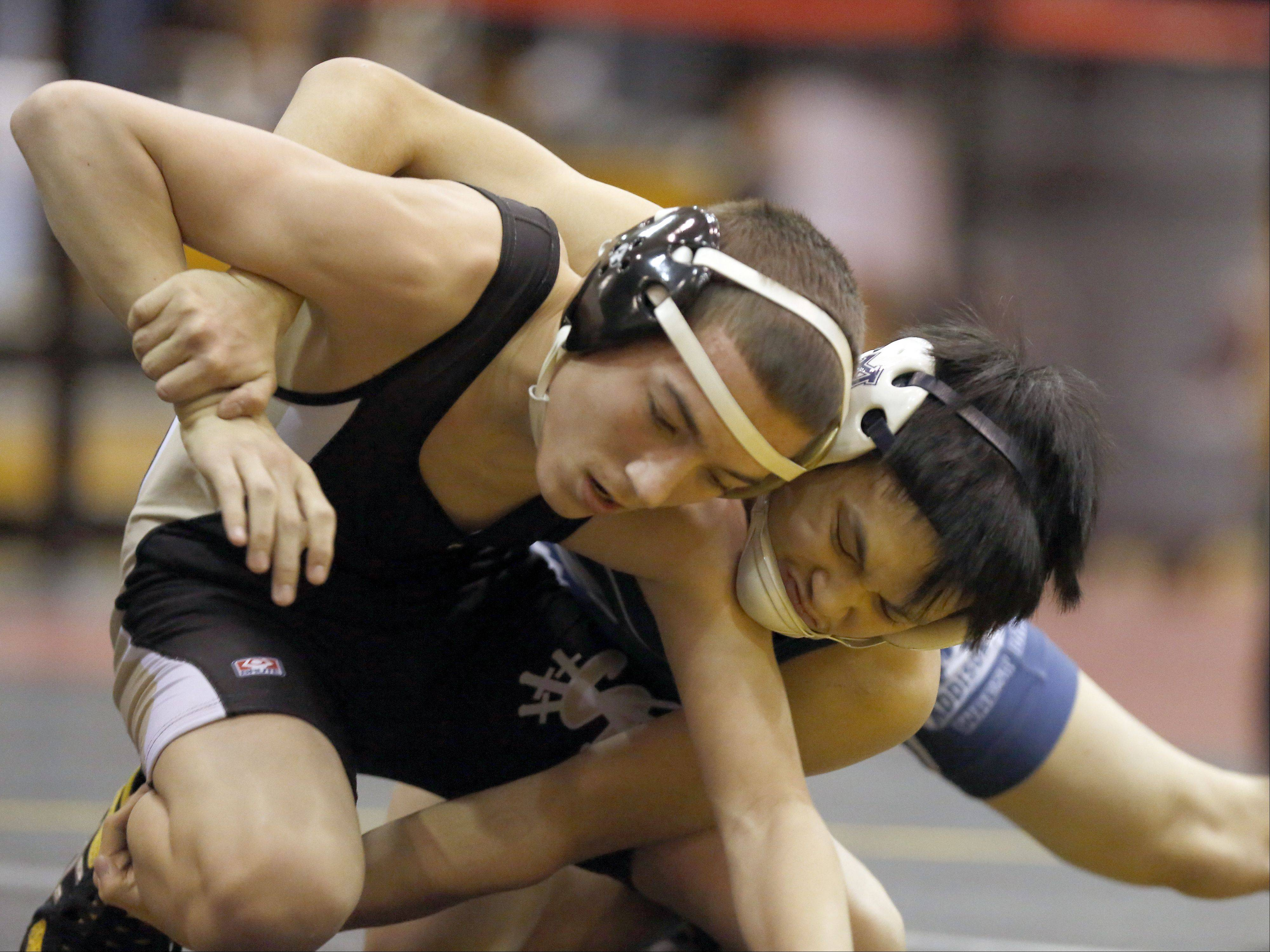 Streamwood's Brandon Schockey, left, wrestles Addison Trail's Kris Santiago in the 106 pound weight class Saturday, January 18, 2014 at the Batavia wrestling invite.