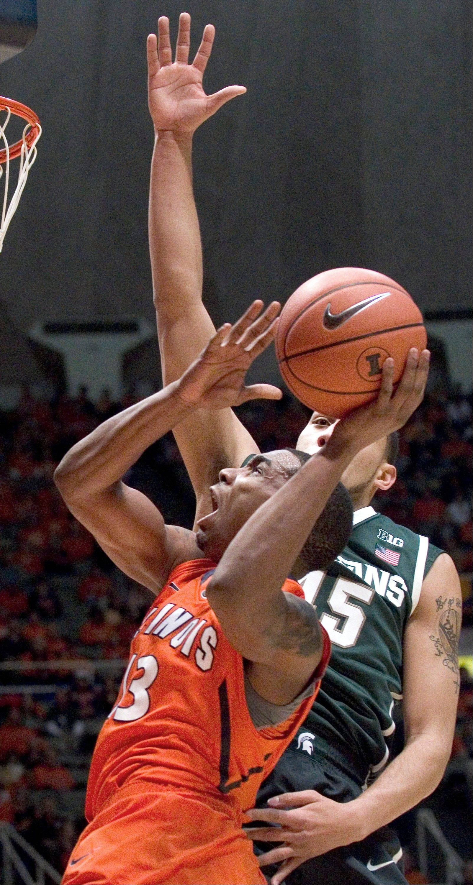 Illinois' Tracy Abrams (13) looks for a shot against Michigan State's Denzel Valentine (45) during Saturday night's game in Champaign. The Illini lost 78-62.