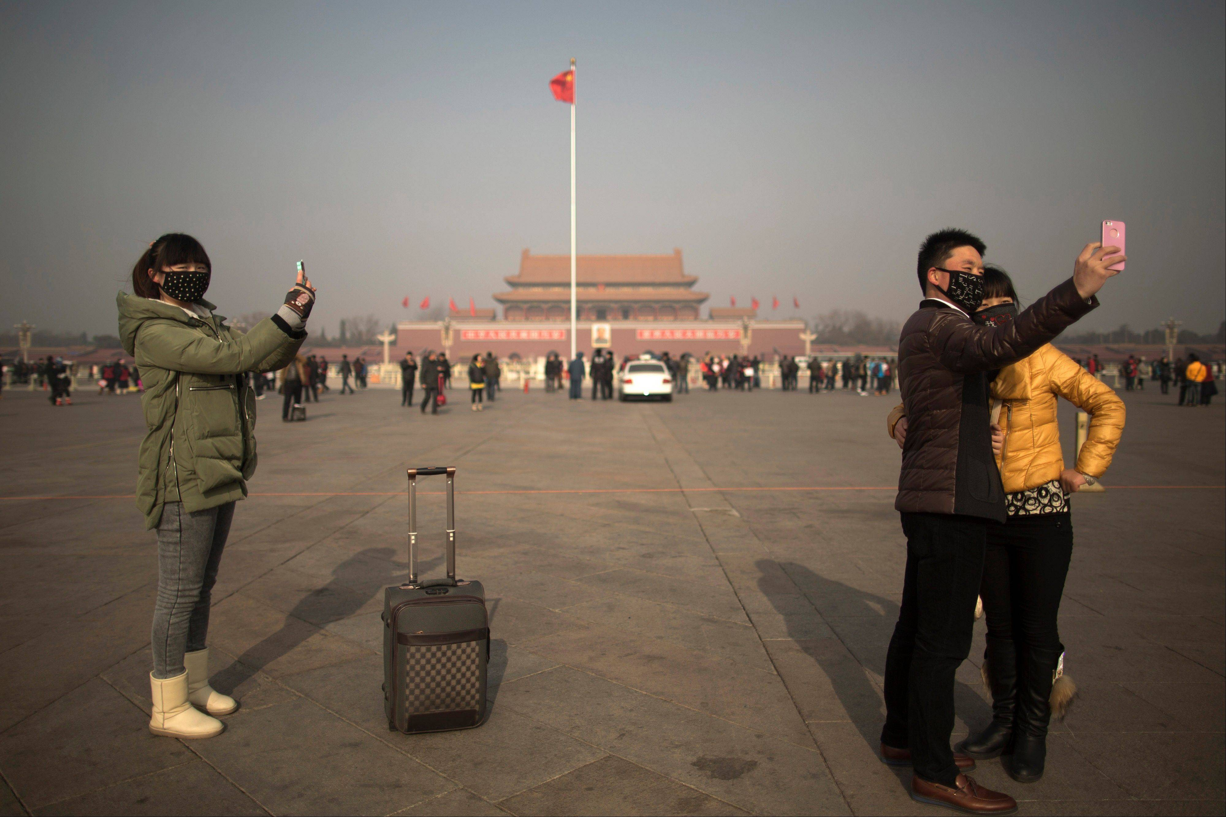 Tourists in masks use mobile phone cameras to snap shots of themselves during a heavily polluted day on Tiananmen Square in Beijing, China, Thursday. Beijing�s skyscrapers receded into a dense gray smog Thursday as the capital saw the season�s first wave of extremely dangerous pollution, with the concentration of toxic small particles registering more than two dozen times the level considered safe.