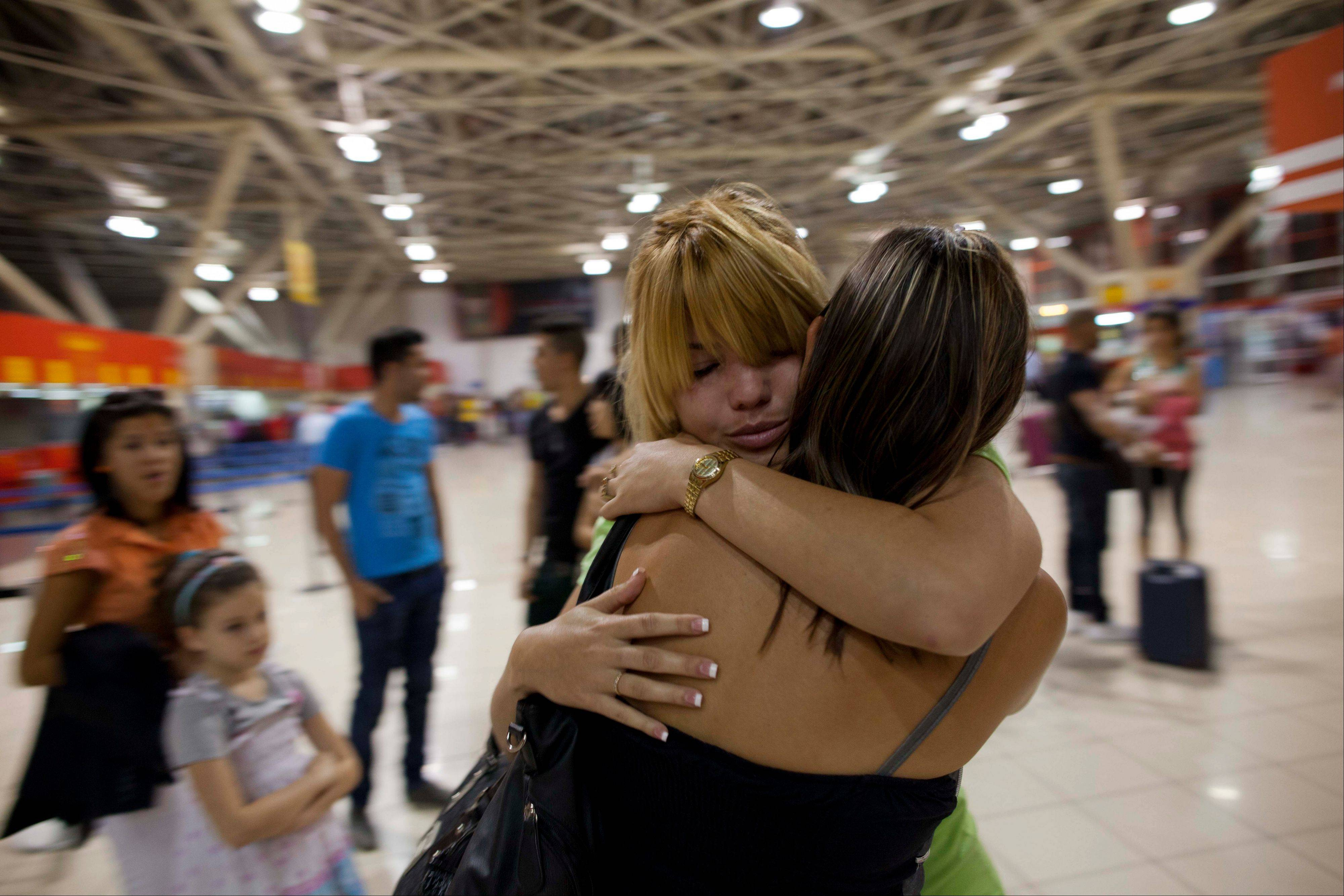 Amalia Reigosa, hugs her sister Jaynet goodbye at the Jose Marti International Airport in Havana, Cuba, before her trip to Milan, Itlay. Reigosa was one of the first Cubans to take advantage of a travel reform that went into effect a year ago this week, when the government scrapped an exit visa requirement that for five decades had made it difficult for most islanders to go abroad.