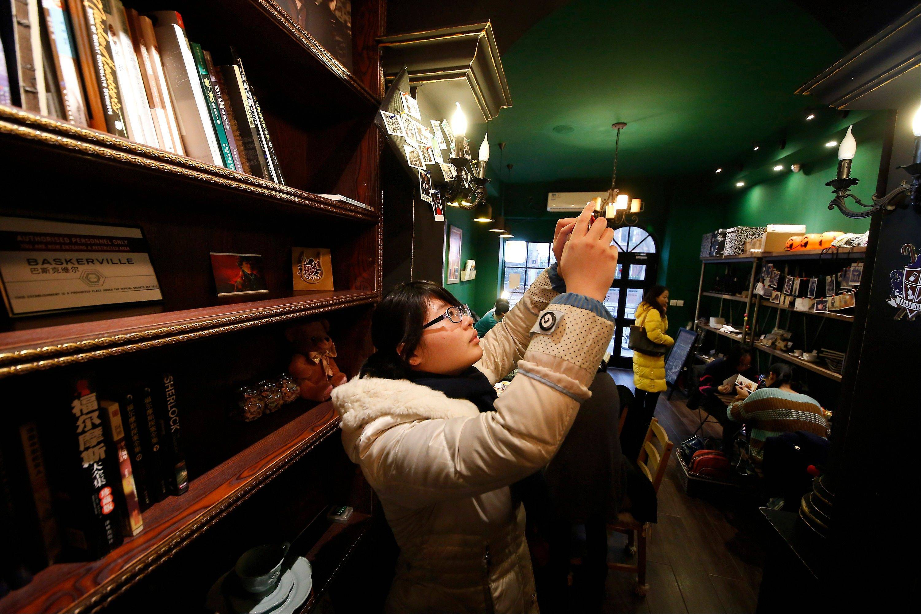 A girl takes pictures at a �Sherlock�-themed cafe in Shanghai, China. �Sherlock has become a global phenomenon, but nowhere more than in China, where fans� devotion is so intense that the BBC says this was the first country outside Britain where the new season was shown.