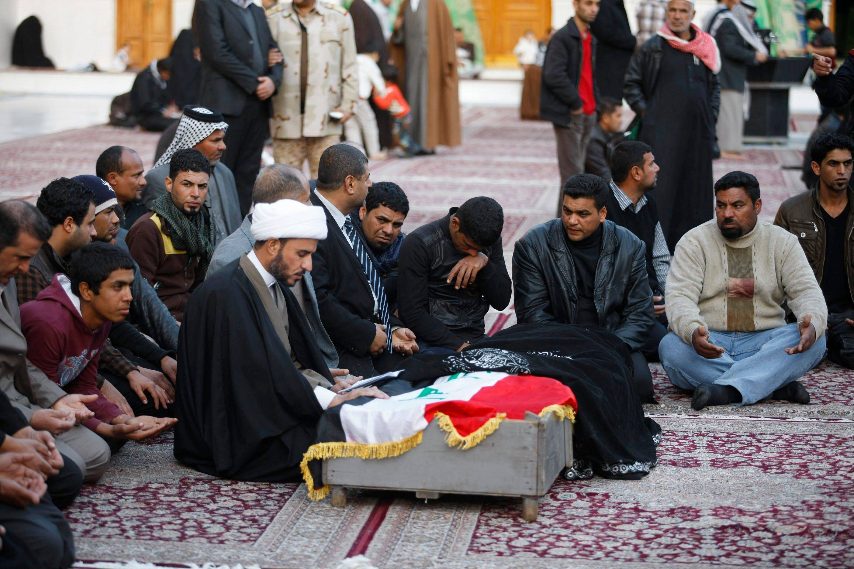 Mourners pray over the coffin of a man killed in a bomb attack during a funeral in the Shiite holy city of Najaf, 100 miles south of Baghdad, Iraq, Sunday. Violence across Iraq, including a series of car bombings and fighting between militants and government troops over control of the country's contested Anbar province, killed dozens Saturday, officials said.