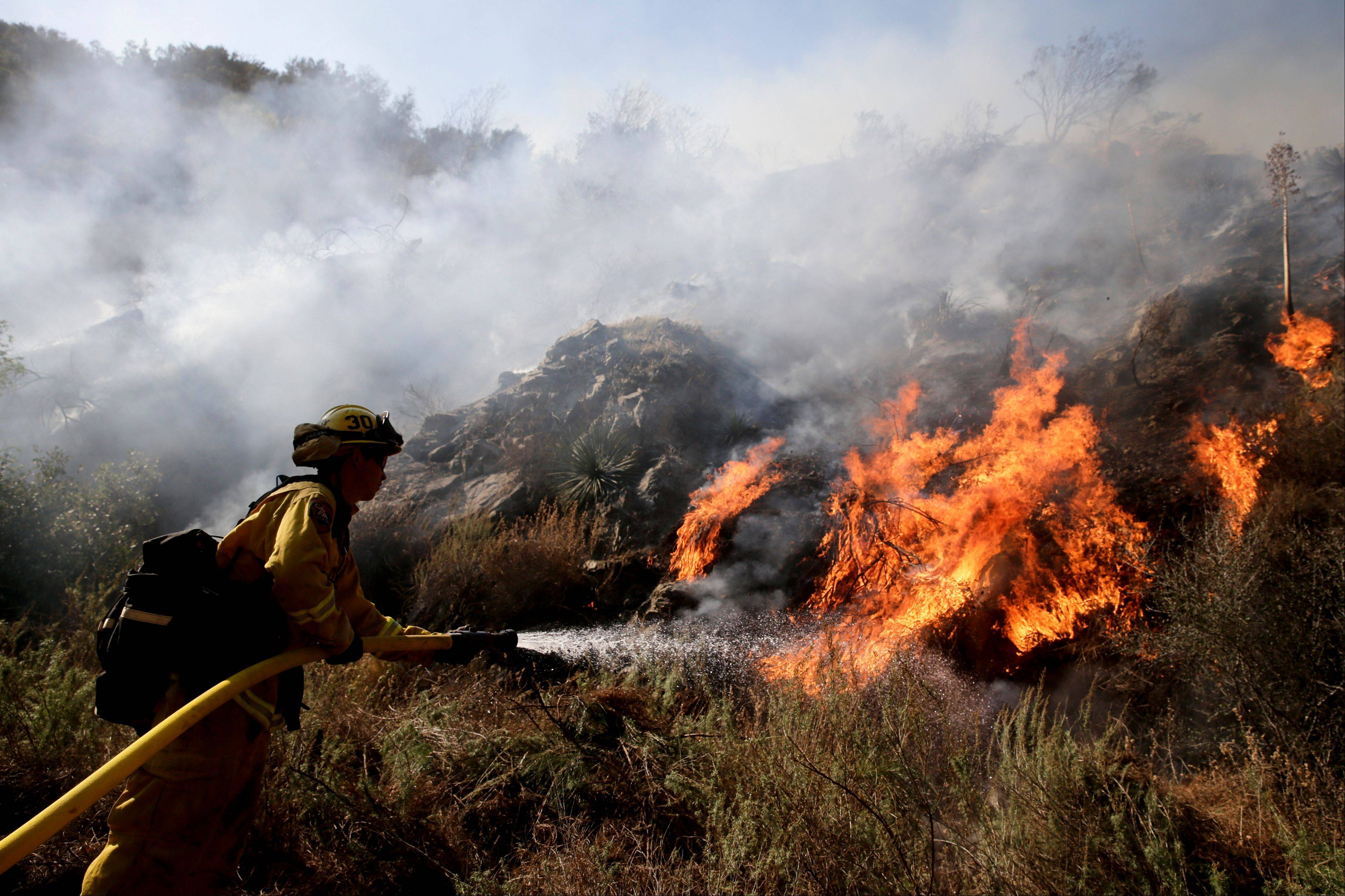 Firefighter Jeff Newby sprays water as he battles the Colby Fire on Friday near Azusa, Calif.