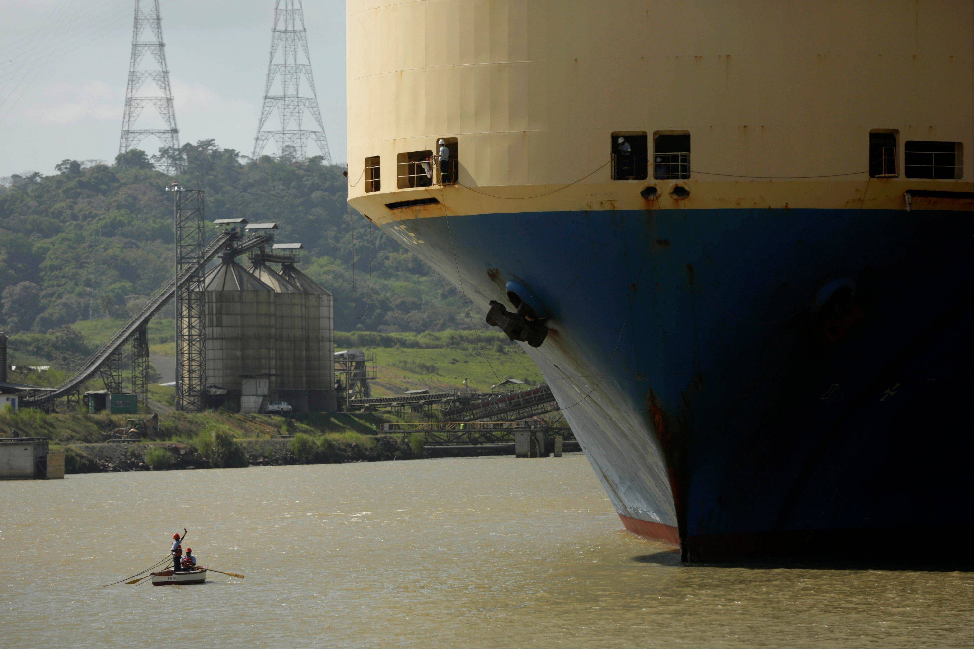 A small boat takes in a line of rope from a cargo ship while entering to the Pedro Miguel locks at the Panama Canal near Panama City. The current canal expansion project would double its capacity.