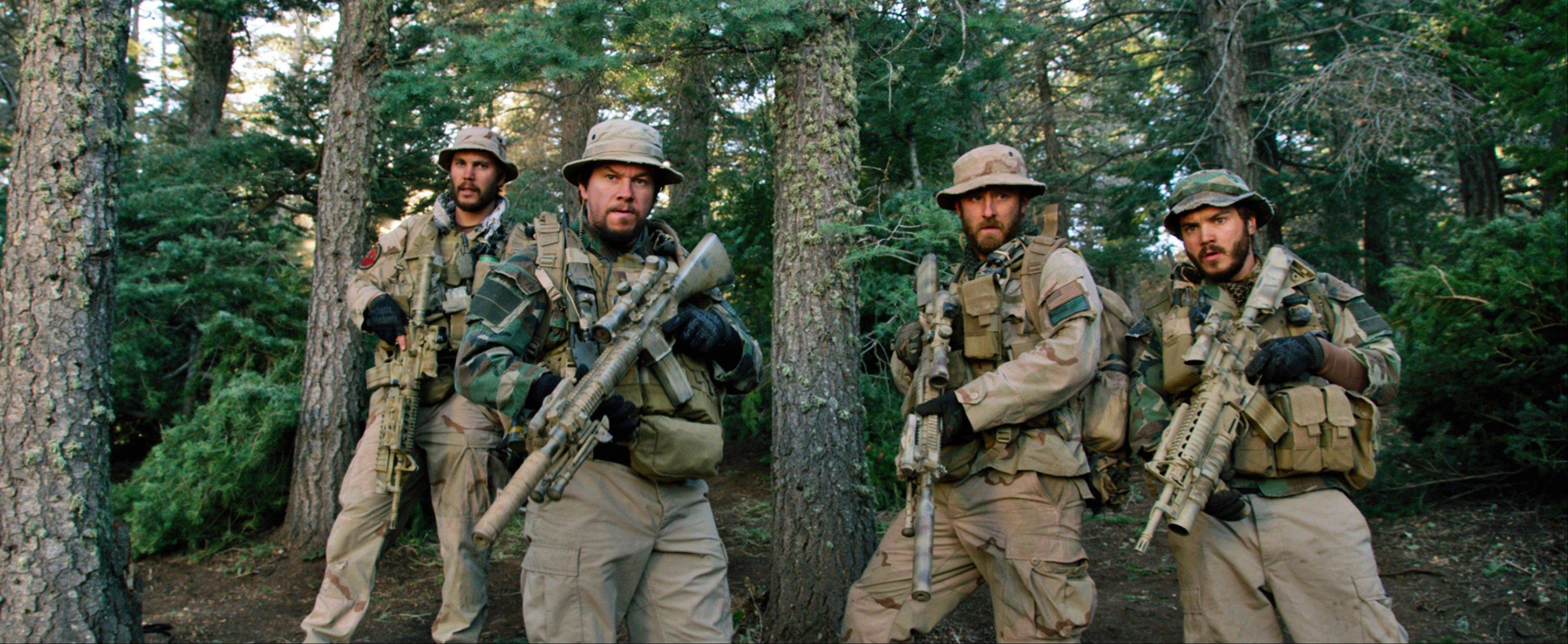 "This photo released by Universal Pictures shows, from left, Taylor Kitsch, as Michael Murphy, Mark Wahlberg as Marcus Luttrell, Ben Foster as Matt �Axe� Axelson, and Emile Hirsch as Danny Dietz in a scene from the film, ""Lone Survivor."" The Navy SEAL drama earned $23.2 million in its second weekend of wide release."