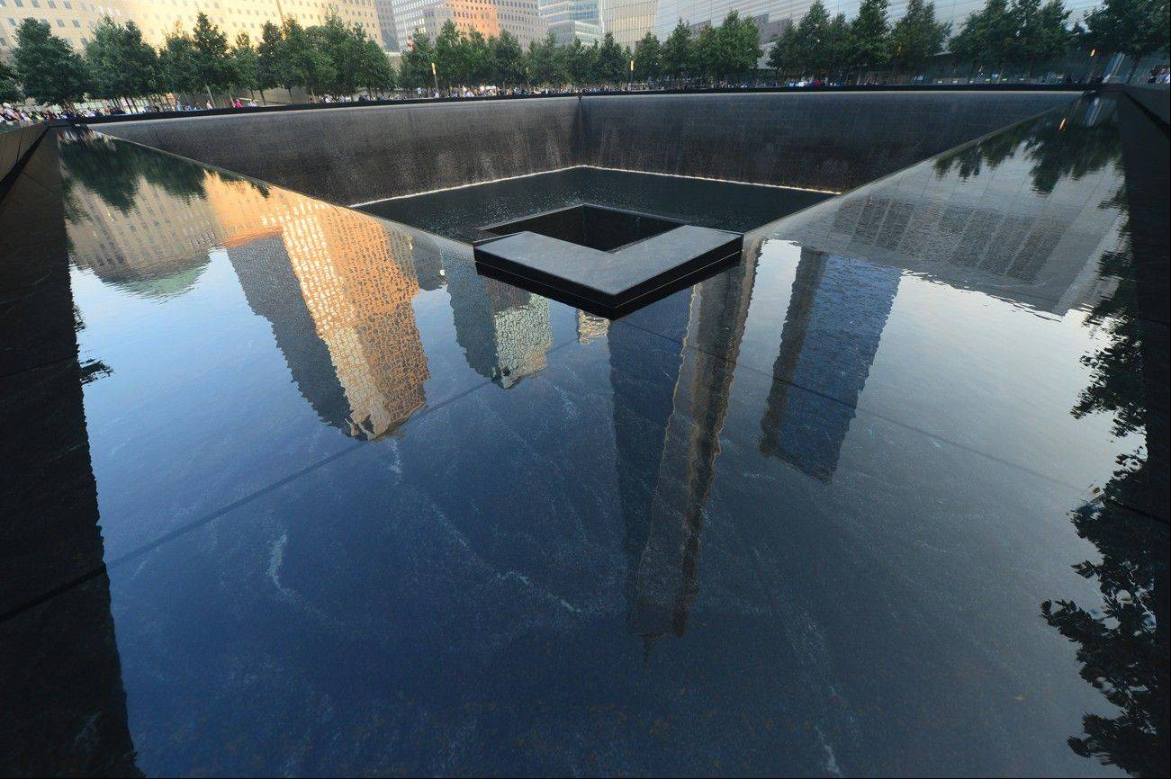 One World Trade Center, center, is reflected on the polished wall of the September 11 Memorial in New York City. The 9/11 Memorial is one of a number of relatively new must-see attractions for Super Bowl fans visiting the New York City area.