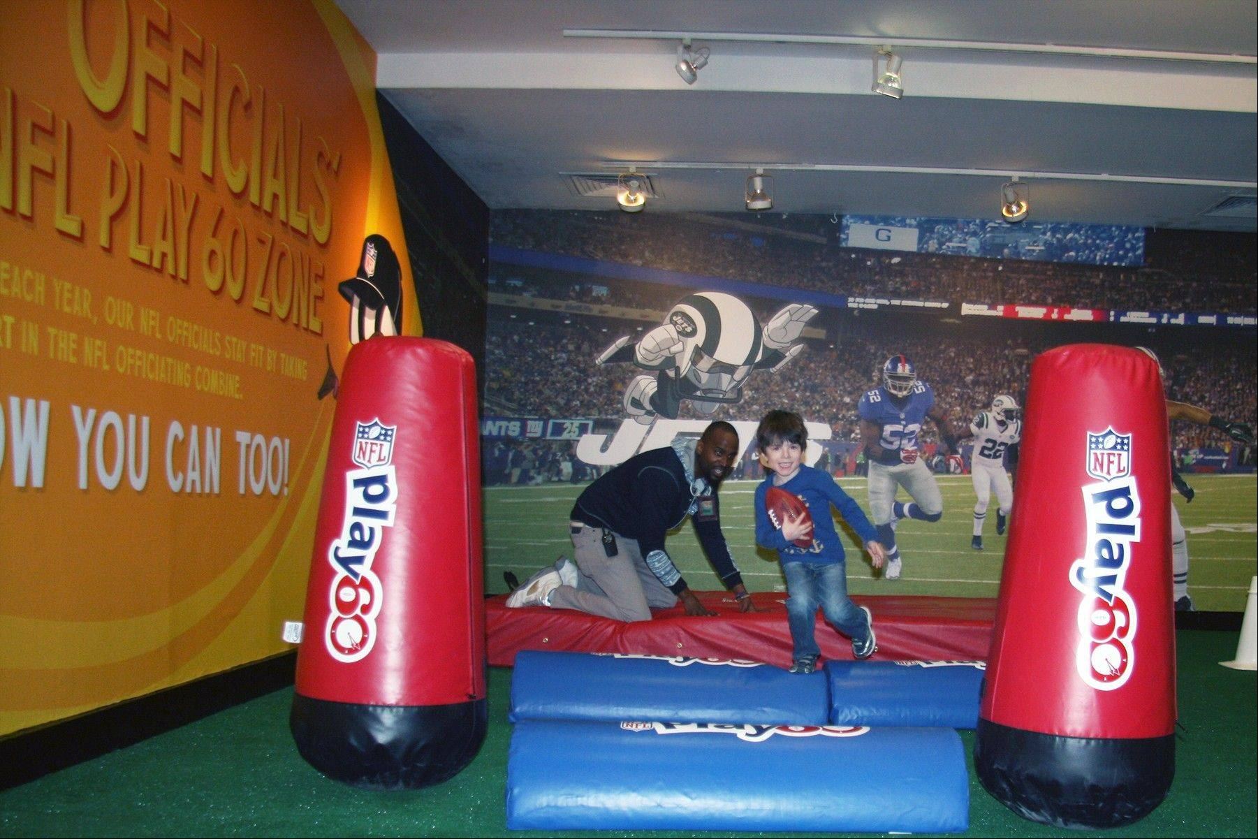"A boy runs through an interactive NFL-themed exhibit at the Children's Museum of Manhattan. The exhibit, called ""You Make the Call: Learn to be An NFL Official,"" runs through Feb. 28."