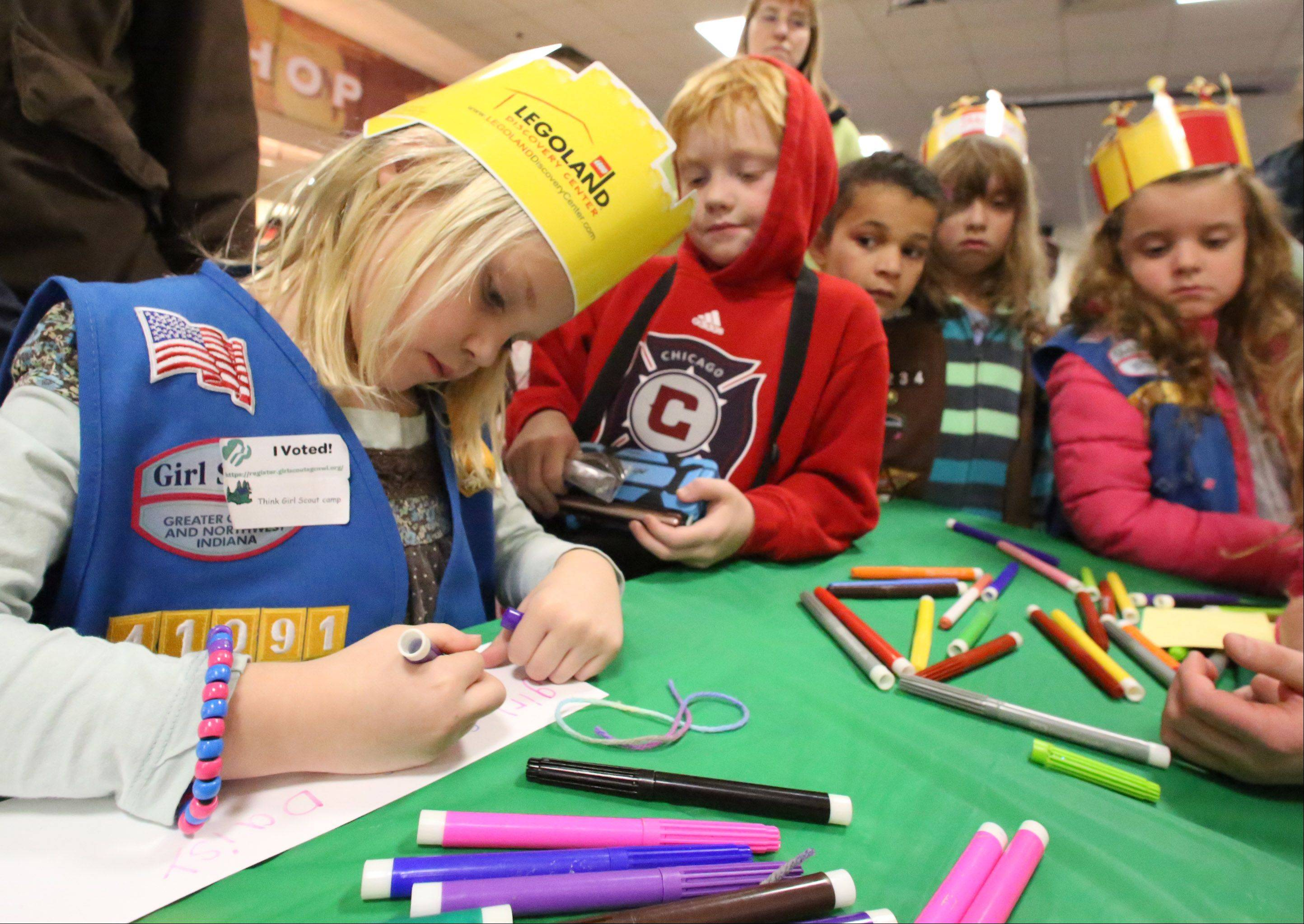 Chloe Eizenga, 6, of Elk Grove Village, with troop 41091, makes a chef hat at the fifth annual Girl Scouts Cookie Kickoff Rally held at Allstate Arena on Saturday in Rosemont.