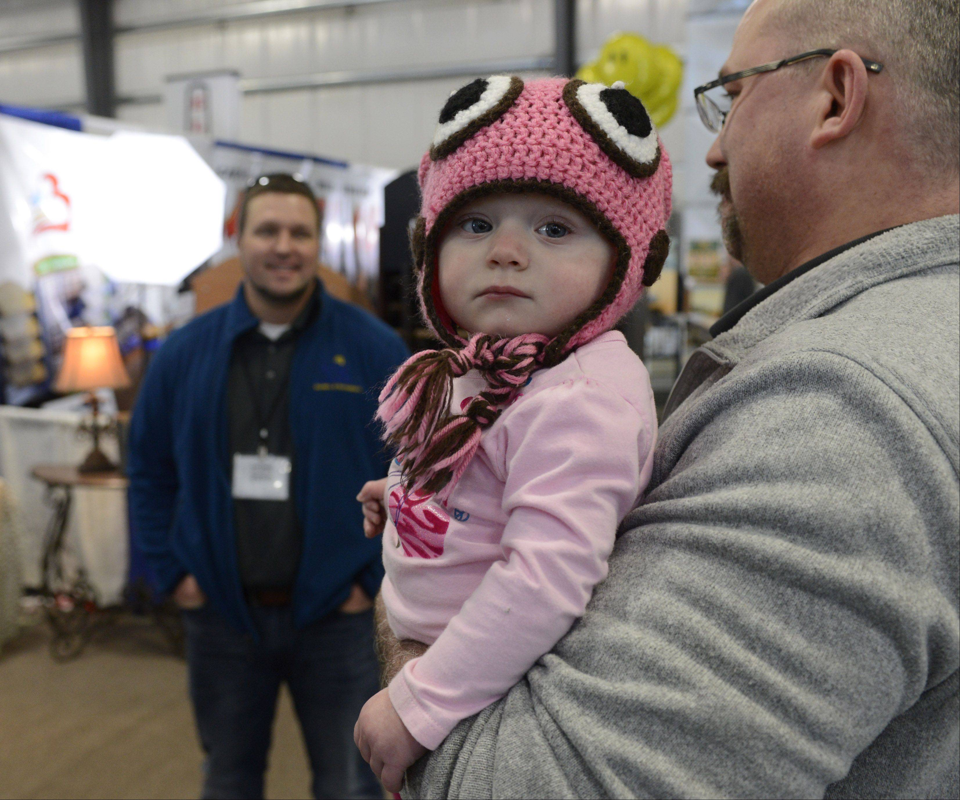 Sofia Leifer, 13 months, waits as her dad, Brett, of Energy Jacket, Crystal Lake, talks with fellow exhibitor Ryan Roggy of RC Contractors, Antioch, during the Home Building and Remodeling Expo at the Lake County Fairgrounds in Grayslake Sunday.