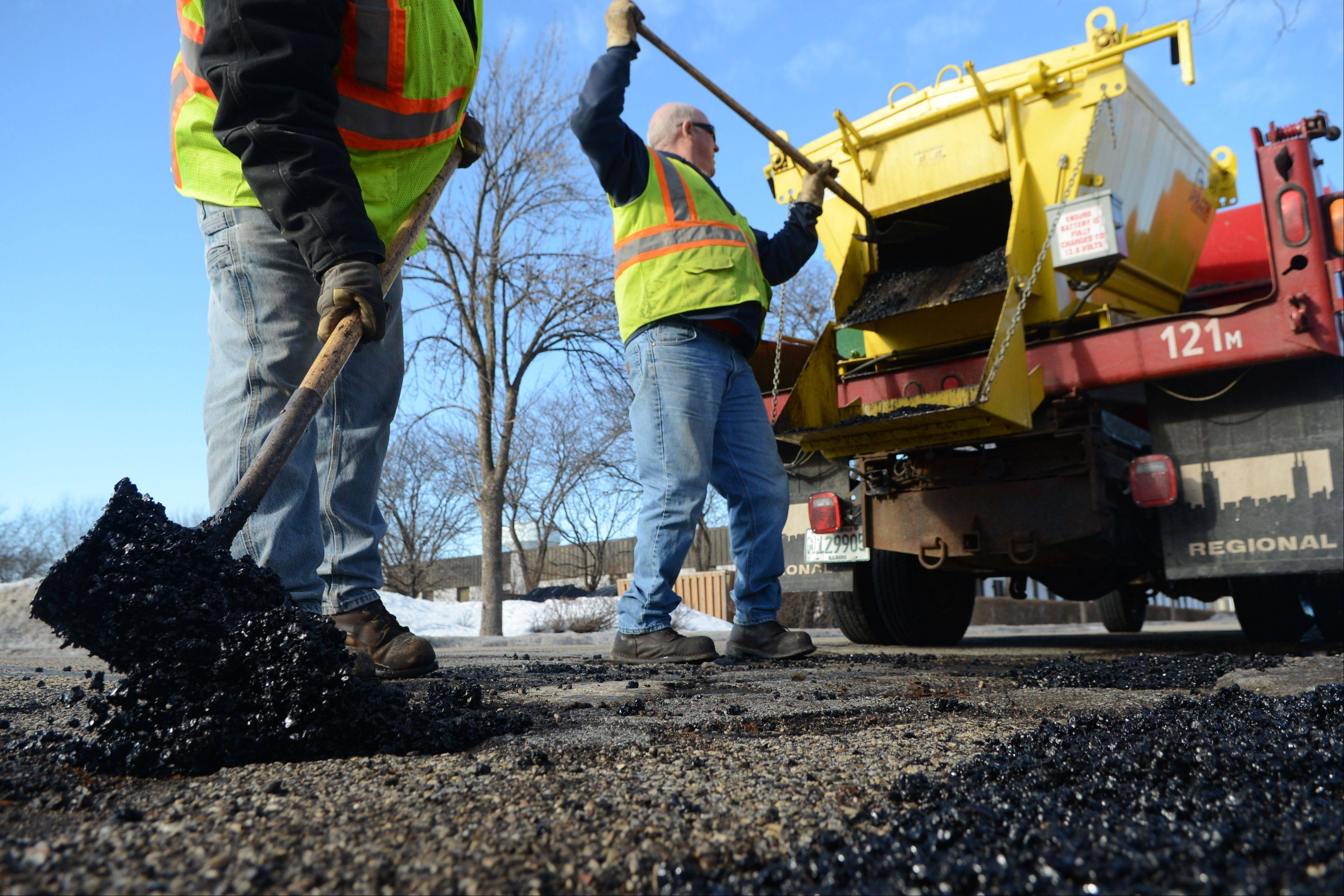 Arlington Heights Public Works employees Terry Koeppl, left, and Ken Tullar, fill potholes on Tonne Road Monday afternoon. The potholes were wide, but not deep, along the road. Koeppl said they want to patch them when they are like this so they don't turn into bigger potholes.